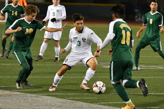 Thousand Oaks High's David Trautman dribbles through traffic against Moorpark's Sean Desmond, left, and Alejandro Sosa during the teams' nonleague match on Nov. 20.