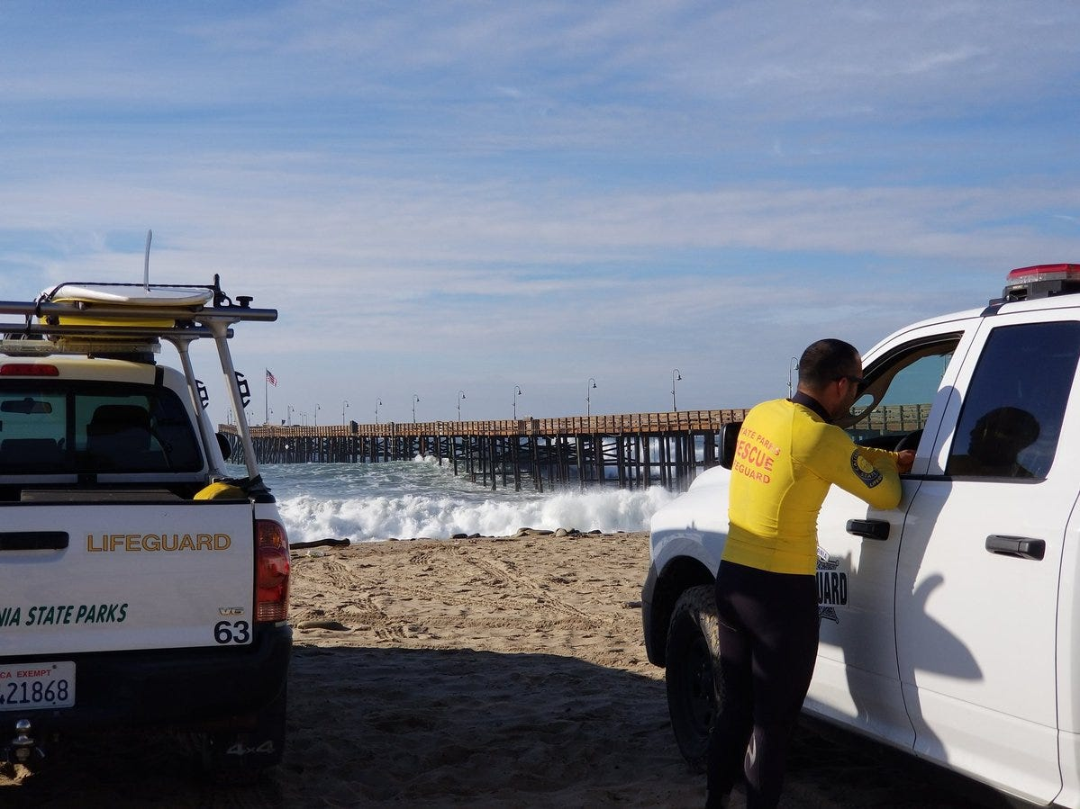 Lifeguard Joey Hernandez, left, talks to fellow lifeguard Casey Lysdale from the beach near the Ventura Pier. High surf in the area prompted city officials to close the pier.