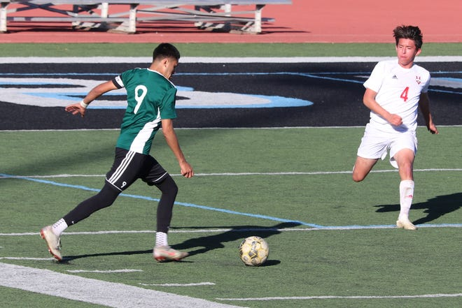 Pacifica High senior attacker Bryant Lobato, left, takes on Hueneme senior centerback Ulises Aragon during the championship game of the Buena High holiday tournament on Dec. 29. Pacifica won the match, 2-1, and the tournament.