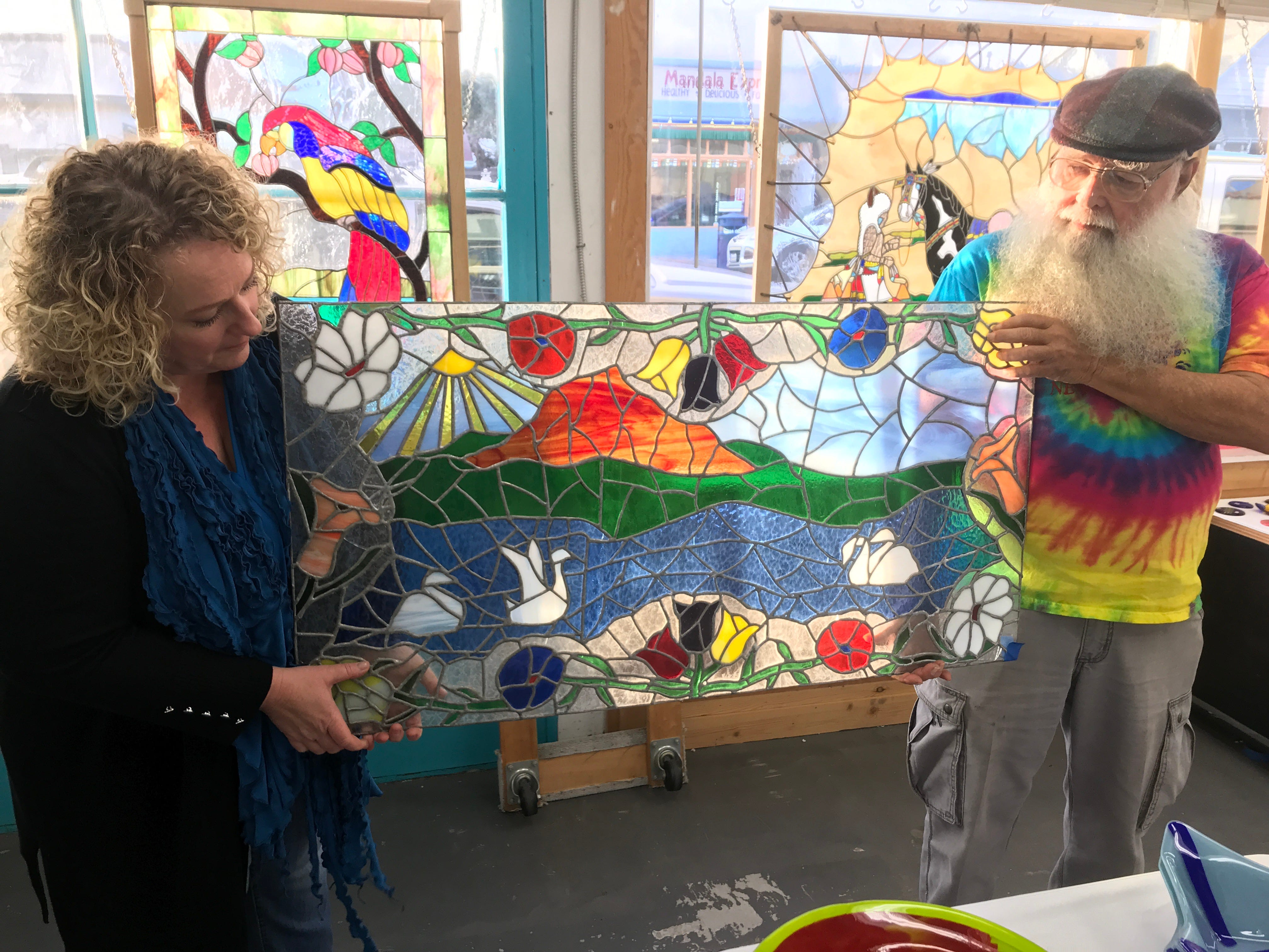 "Glass artist Beglar ""Chief"" Merlich and his daughter, Jennifer, hold up the artist's first piece of work. Merlich created it around 1980 for his then-wife who wanted something nice to hang in their new house. It sparked Merlich's decades-long glass art career."