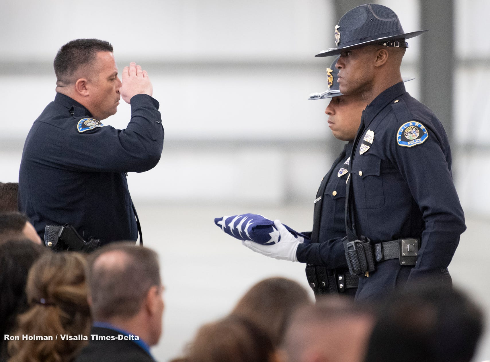 Tulare Interim Police Chief Matt Machado, left, salutes officers Jonathan Zequeida, left, and Eric Wilson after they folded a U.S. flag during a memorial for Tulare Police K-9 officer Bane on Wednesday, January 9, 2019. Bane was killed during an officer-involved shooting on December 9 of last year.