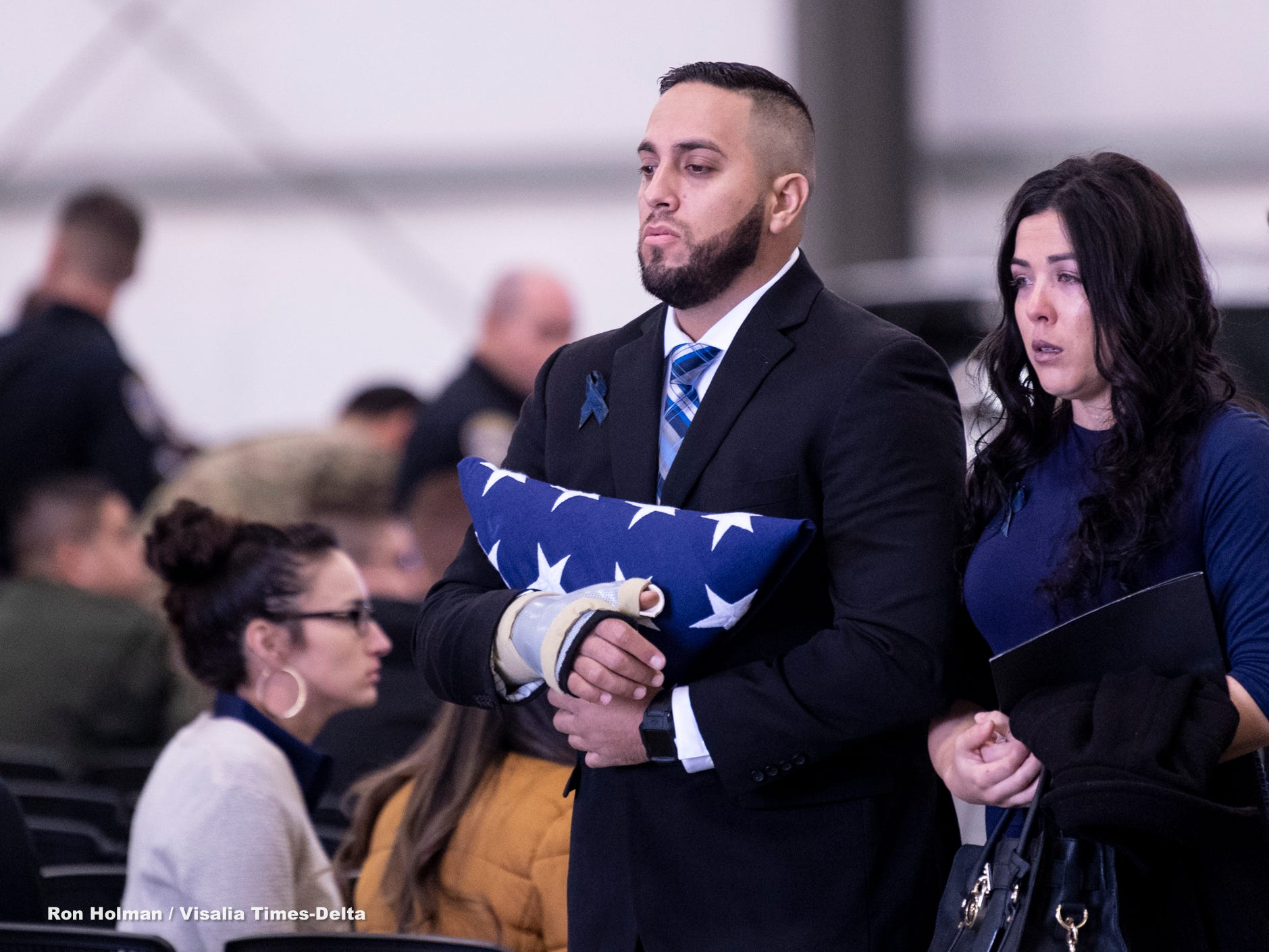 Officer Ryan Garcia, left, leaves Wednesday's memorial for his fallenTulare Police K-9 partner Bane. Bane was killed during an officer-involved shooting on December 9 of last year and is credited with saving Garcia's life.
