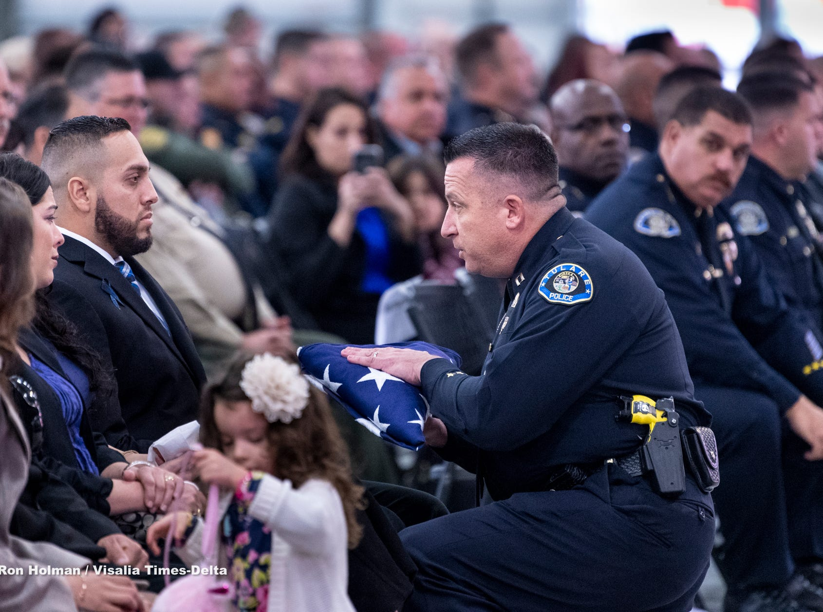 Tulare Interim Police Chief Matt Machado, right, presents a folded U.S. flag to Officer Ryan Garcia on Wednesday, January 9, 2019 during a memorial for Garcia's fallenTulare Police K-9 partner Bane. Bane was killed during an officer-involved shooting on December 9 of last year and is credited with saving Garcia's life.