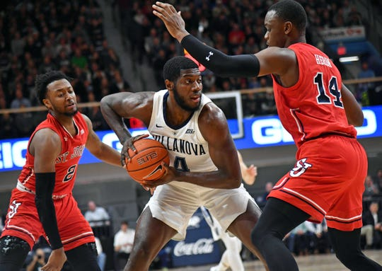 Jan 8, 2019; Villanova, PA, USA; Villanova Wildcats forward Eric Paschall (4) is double teamed by St. John's Red Storm guard Shamorie Ponds (2) and guard Mustapha Heron (14) during the first half at Finneran Pavilion.