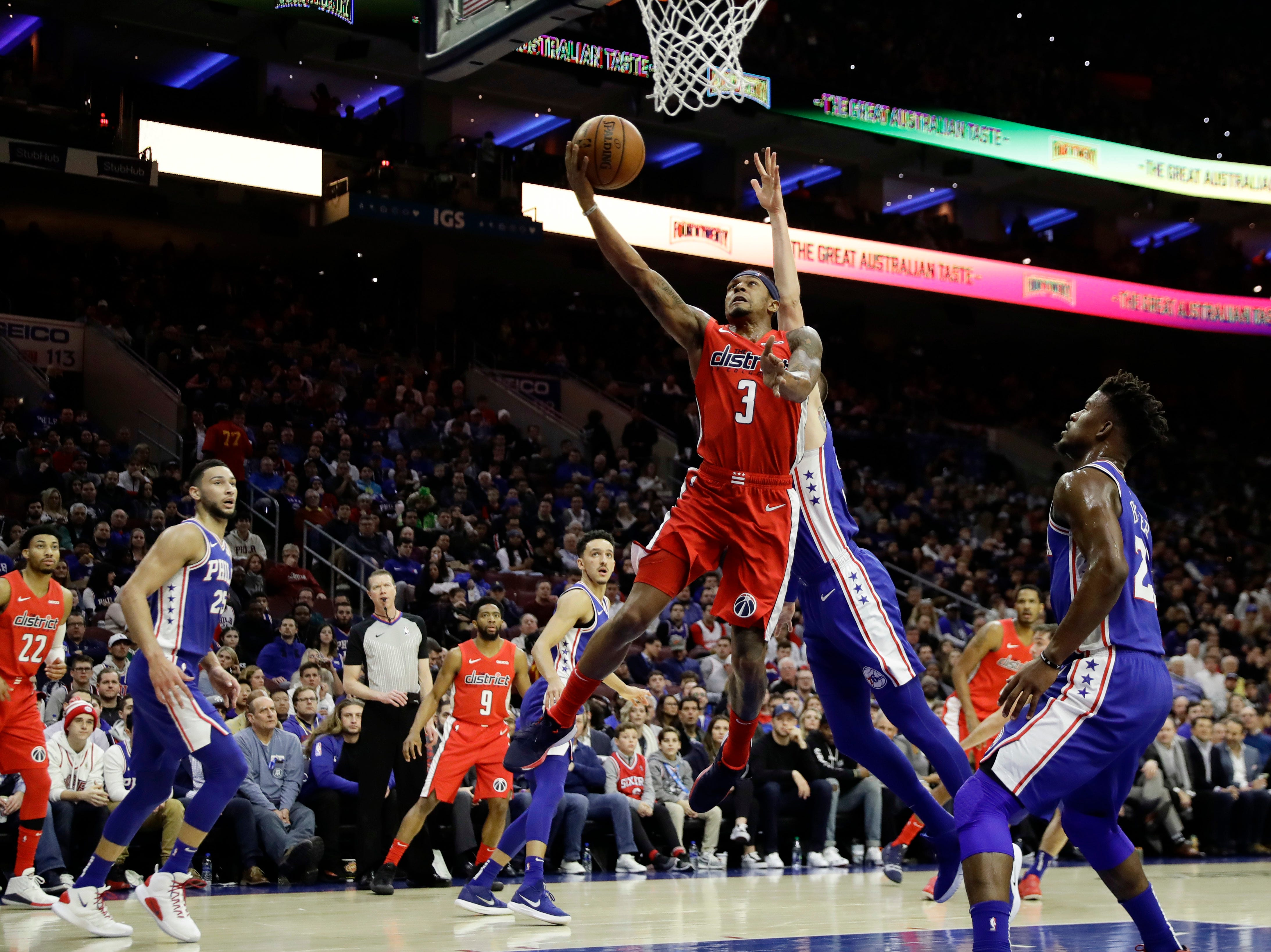 Washington Wizards' Bradley Beal, left, goes up for a shot past Philadelphia 76ers' Mike Muscala during the first half of an NBA basketball game, Tuesday, Jan. 8, 2019, in Philadelphia. (AP Photo/Matt Slocum)