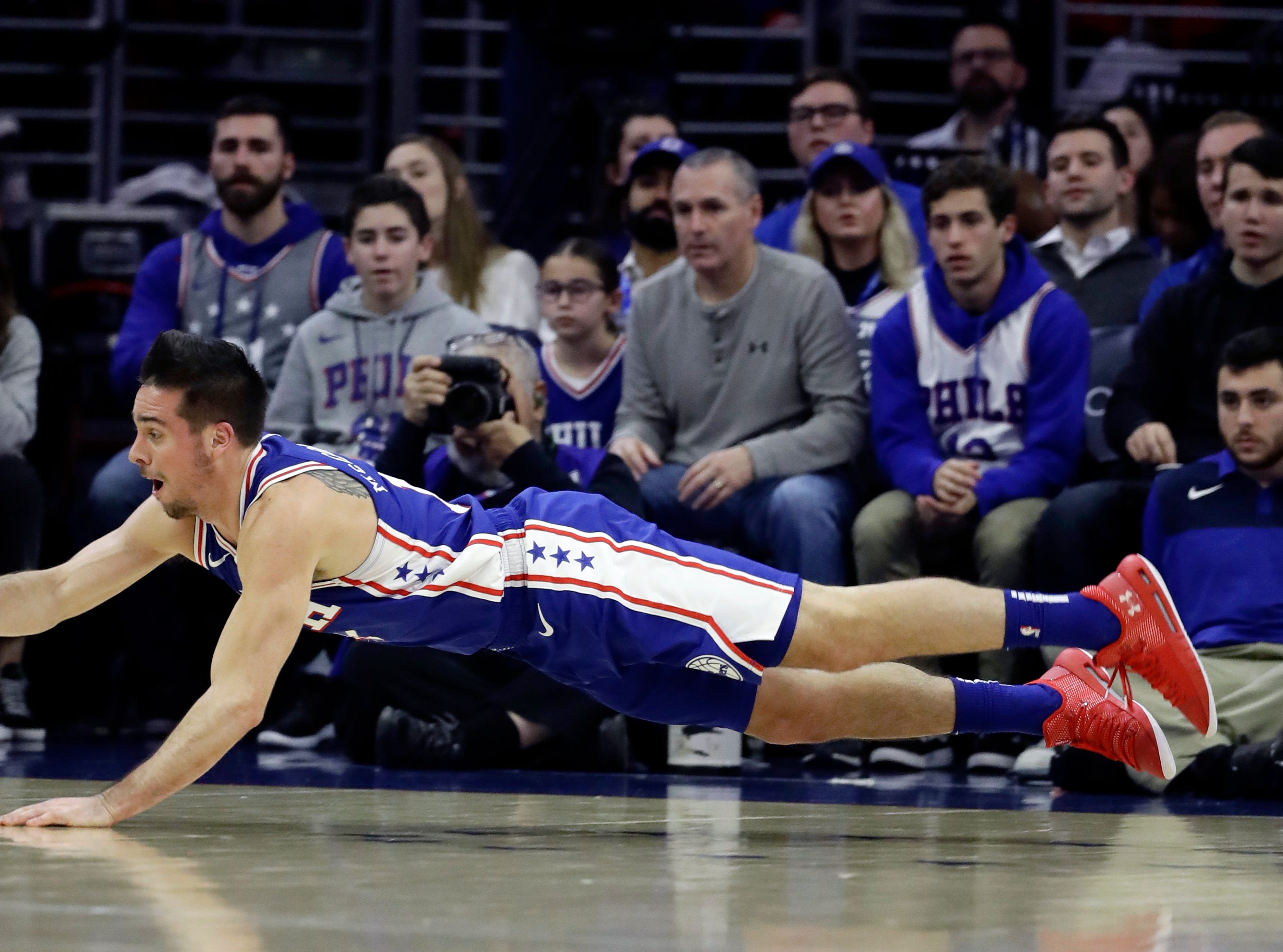 Philadelphia 76ers' T.J. McConnell dives for a loose ball during the first half of an NBA basketball game against the Washington Wizards, Tuesday, Jan. 8, 2019, in Philadelphia. (AP Photo/Matt Slocum)