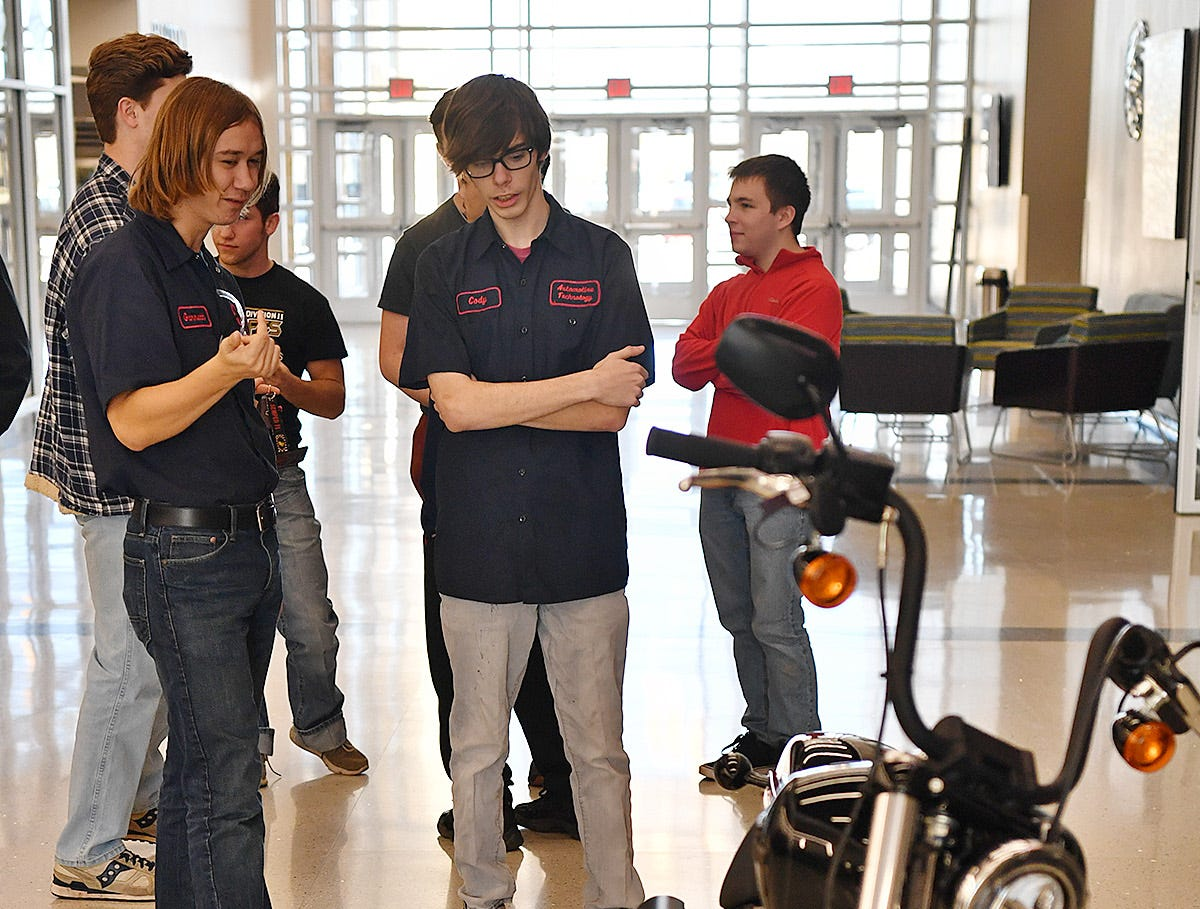 Garrett Koetter, left, and Cody Pierce, automotive technology students at the Career Education Center talks about modifications they and other students will make to a 2019 Harley Davidson motorcycle as part of a nationwide collaboration competition.
