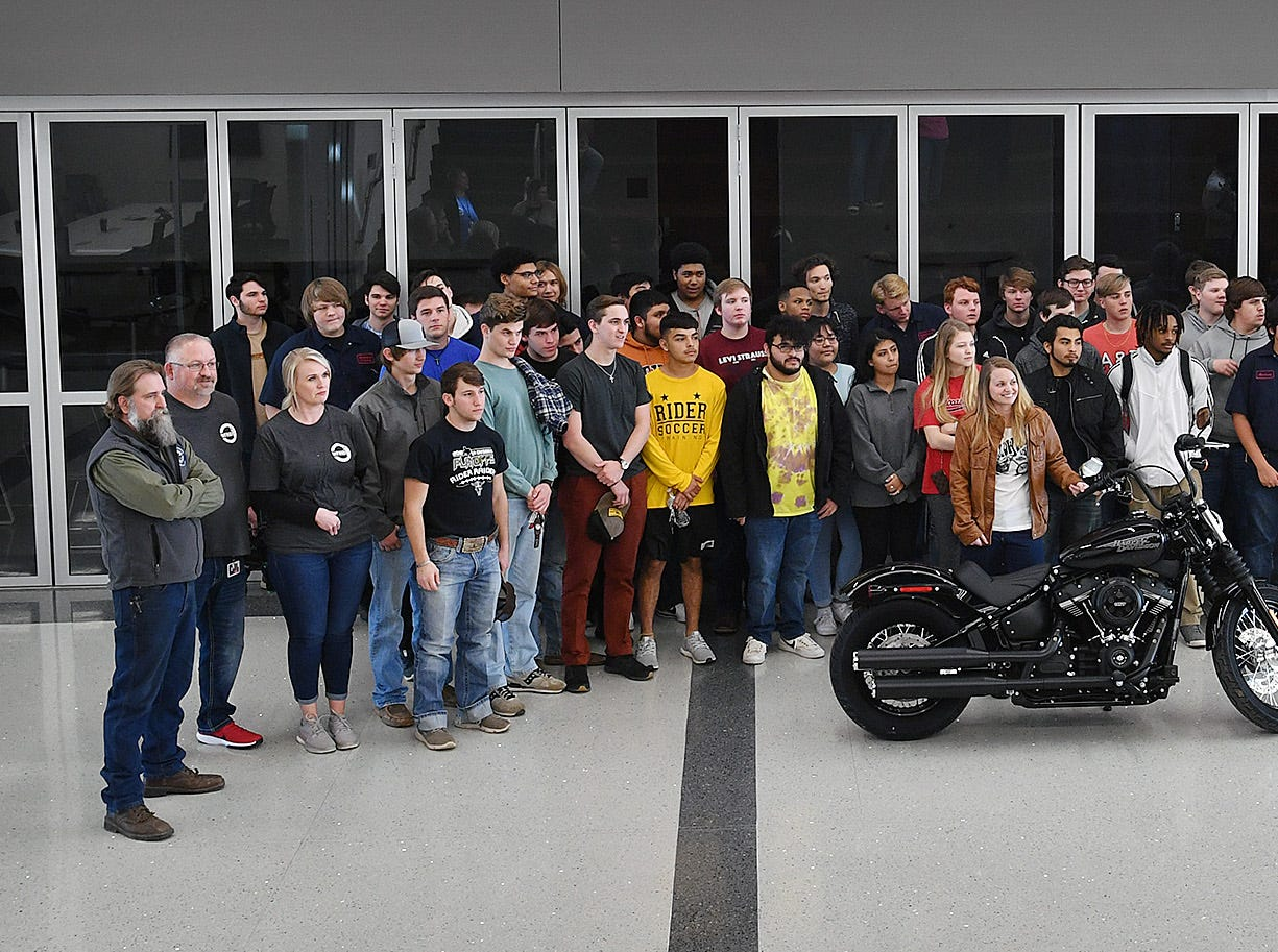 Students from several courses at the Career Education Center are photographed with Bobbie Gilmore, center, of Red River Harley Davidson. They will participate in a nationwide motorcycle customization competion, Battle of the Kings.