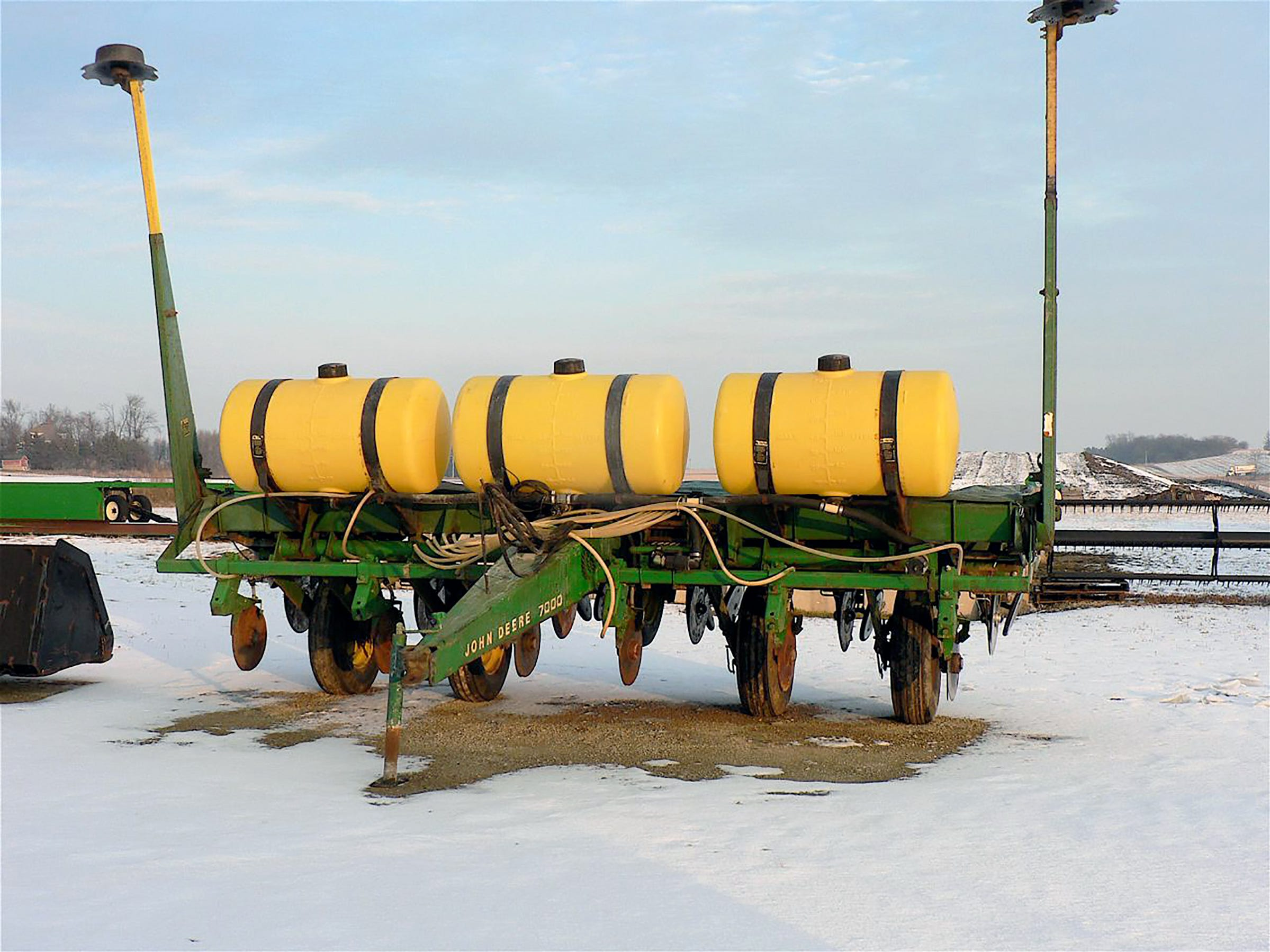 A John Deere 7000 corn planter outside waiting to being sold.