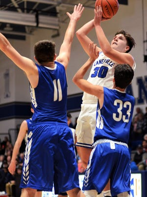 Cobe Curry shoots in the lane over Cambridge's Cody Moore, left, and Jett McElroy during Zanesville's 51-35 win on Tuesday night at Winland Memorial Gymnasium. Curry, a 6-5 senior, scored a game-high 19 points with nine rebounds in his first game back from injury.