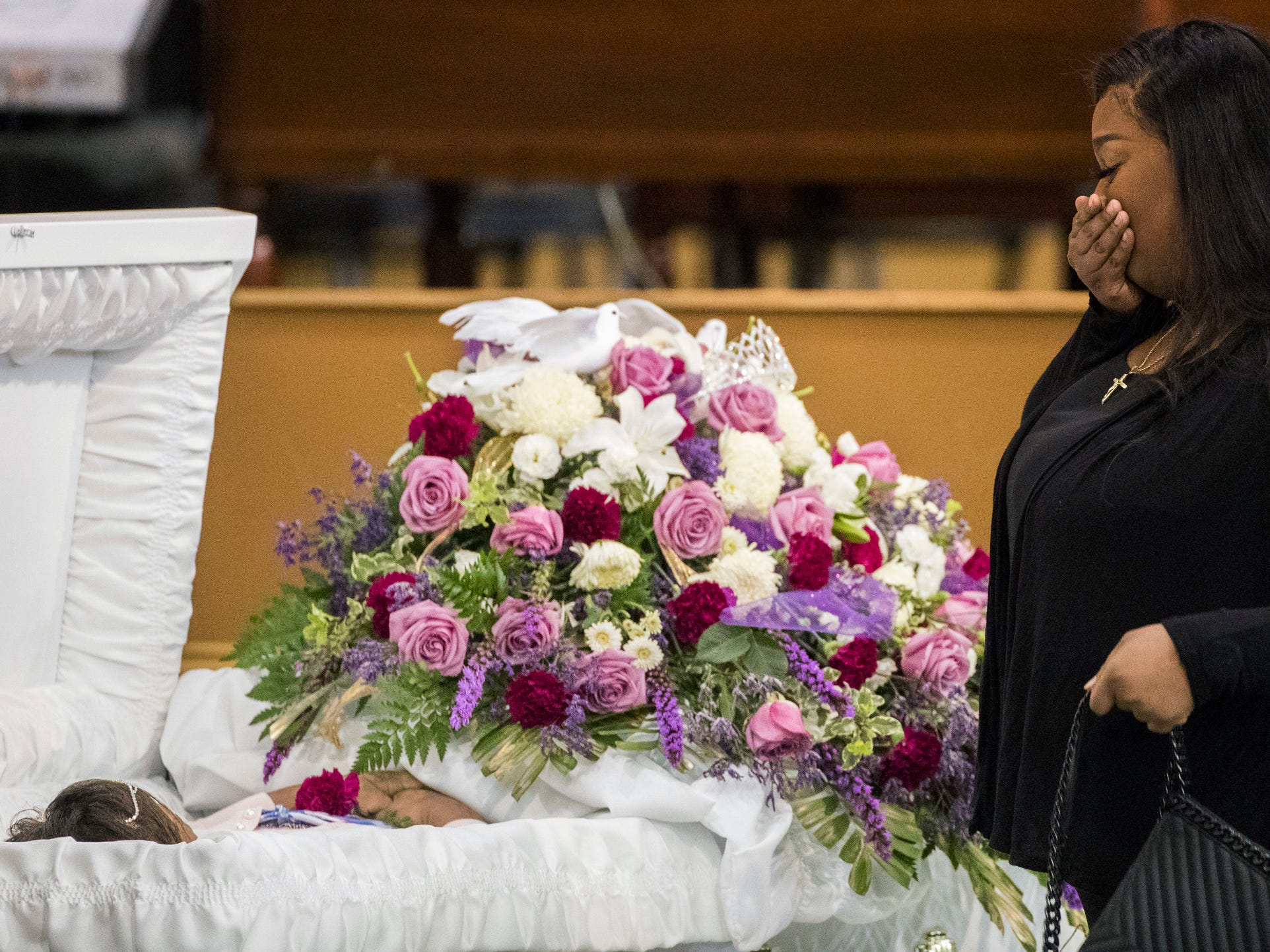 A mourner approaches the casket of Jazmine Barnes during a viewing ceremony before the memorial service.
