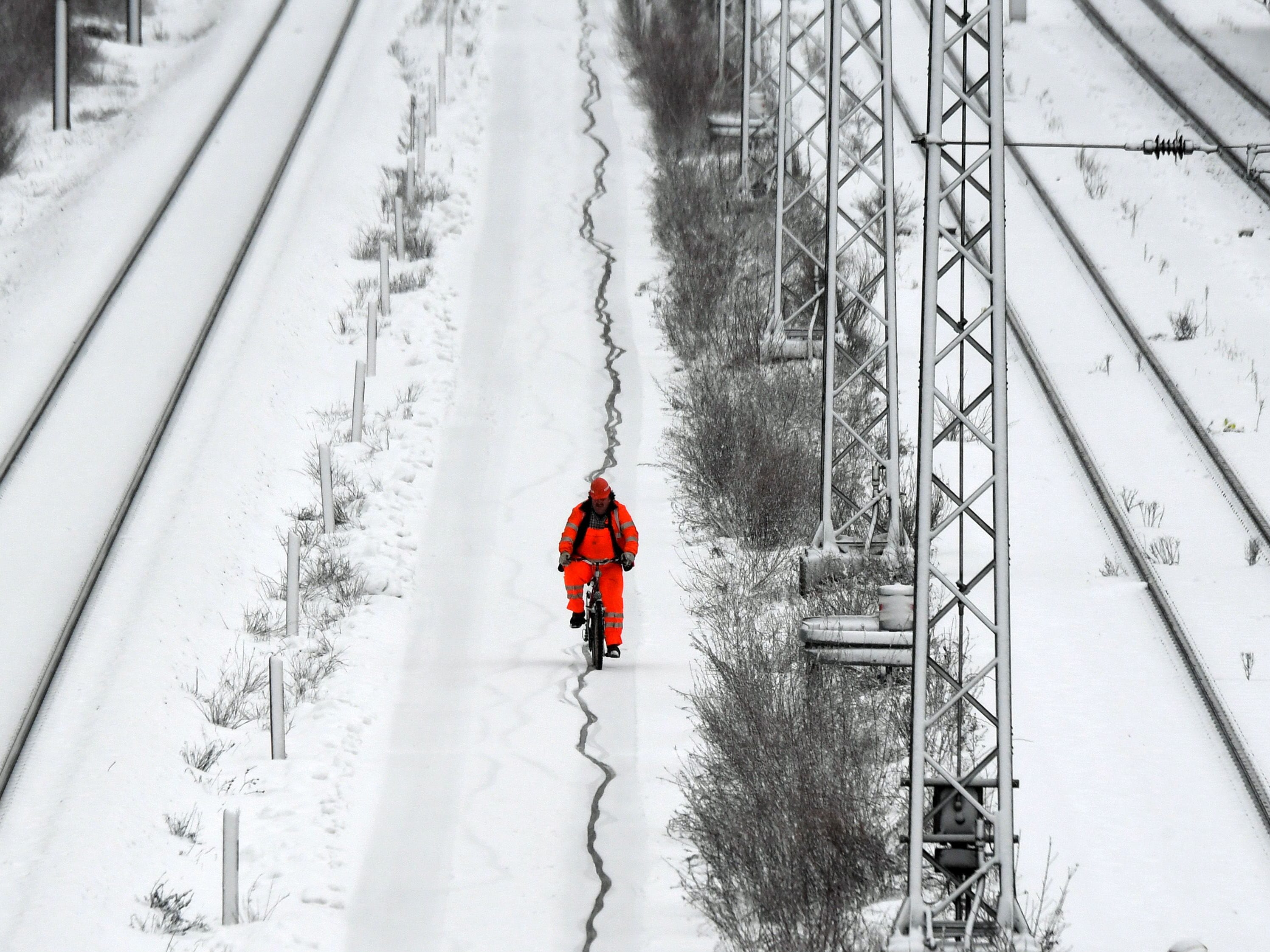 An employee of a freight train terminal cycles his bicycle after snow fall in Munich Germany,  Jan 9. 2019.