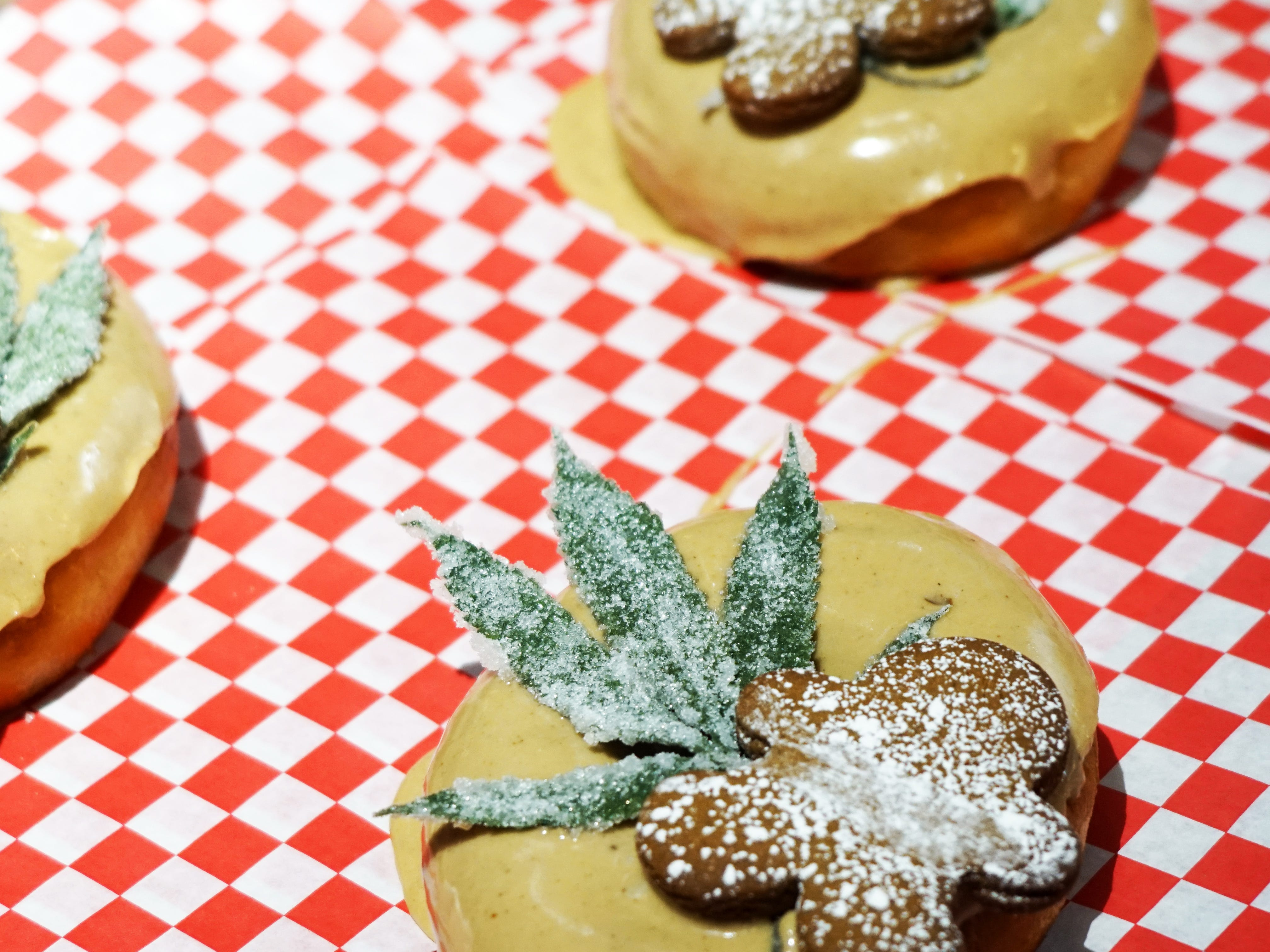 A donut topped with a CBD-infused glaze, a candied hemp leaf and a piece of gingerbread sits on a tray at Glazed & Confuzed donuts in the Stanley Marketplace in Aurora, Colorado.