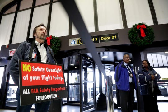 Federal Aviation Administration employee Michael Jessie, who is currently working without pay as an aviation safety inspector for New York international field office overseeing foreign air carriers, holds a sign while attending a news conference at Newark Liberty International Airport, Tuesday, Jan. 8, 2019, in Newark, N.J. U.S. Sens. Cory Booker and Bob Menendez called a news conference at the airport to address the partial government shutdown, which is keeping some airport employees working without pay. (AP Photo/Julio Cortez) ORG XMIT: NJJC101