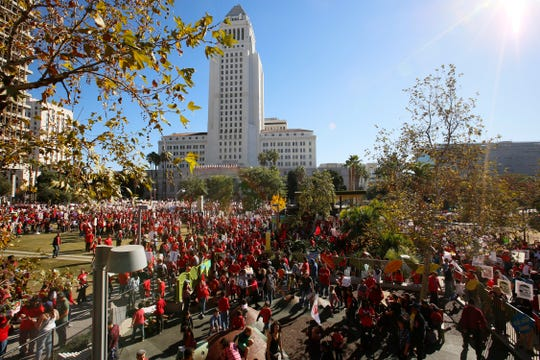 In this Saturday, Dec. 15, 2018, photo, thousands of teachers marched and rallied outside Los Angeles City Hall. Teachers in the nation's second-largest school district will go on strike next month if there's no settlement of its long-running contract dispute, union leaders said Wednesday, Dec. 19. The announcement by United Teachers Los Angeles threatens the first strike against the Los Angeles Unified School District in nearly 30 years and follows about 20 months of negotiations. (AP Photo/Damian Dovarganes) ORG XMIT: CADD306