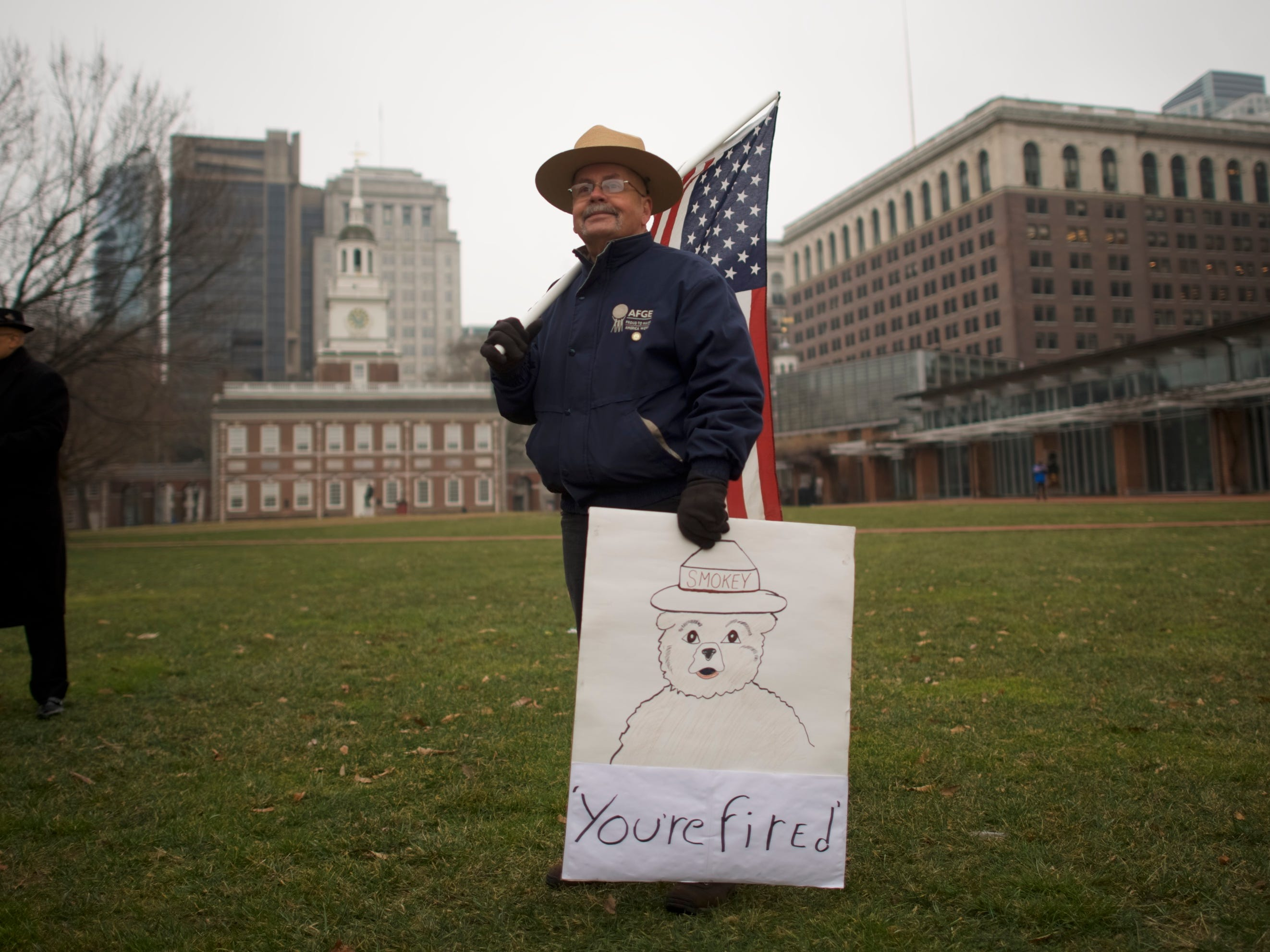 "PHILADELPHIA, PA - JANUARY 08:  David Fitzpatrick, 64, a Park Ranger, holds an American flag and a placard stating ""You're fired"" with ""Smokey the Bear,"" after a protest rally with furloughed federal workers and area elected officials in front of Independence Hall on January 8, 2019 in Philadelphia, Pennsylvania.  The government shutdown, now lasting 18 days, marks the second longest United States in history, affecting about 800,000 federal employees.  (Photo by Mark Makela/Getty Images) ORG XMIT: 775278689 ORIG FILE ID: 1079379668"