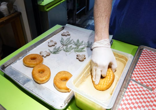 Glazed & Confuzed donuts founder and CEO Josh Schwab frosts a donut with CBD-infused glaze at his shop in the Stanley Marketplace in Aurora, Colorado, before topping each with a candied hemp leaf and gingerbread cutout.