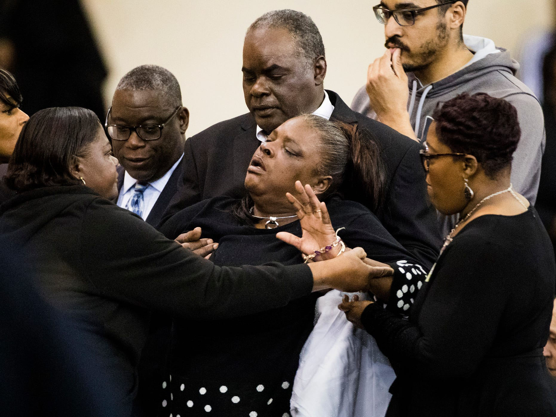 Family members holds one of Jazmine Barnes' grandmothers after she became emotional while walking to the casket.