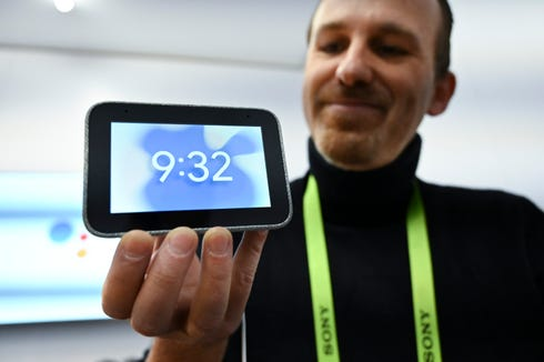 Google's Mert Topcu holds a Lenovo-made Google alarm clock that includes a smart speaker.
