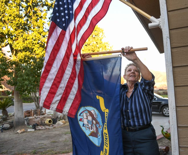 Phyllis Seleska hangs a Navy flag in the front of her home in San Bernardino. Seleska, retired after a 20 year career in the U.S. Navy, broke her wrist and had a difficult time getting treatment at a nearby VA Hospital.