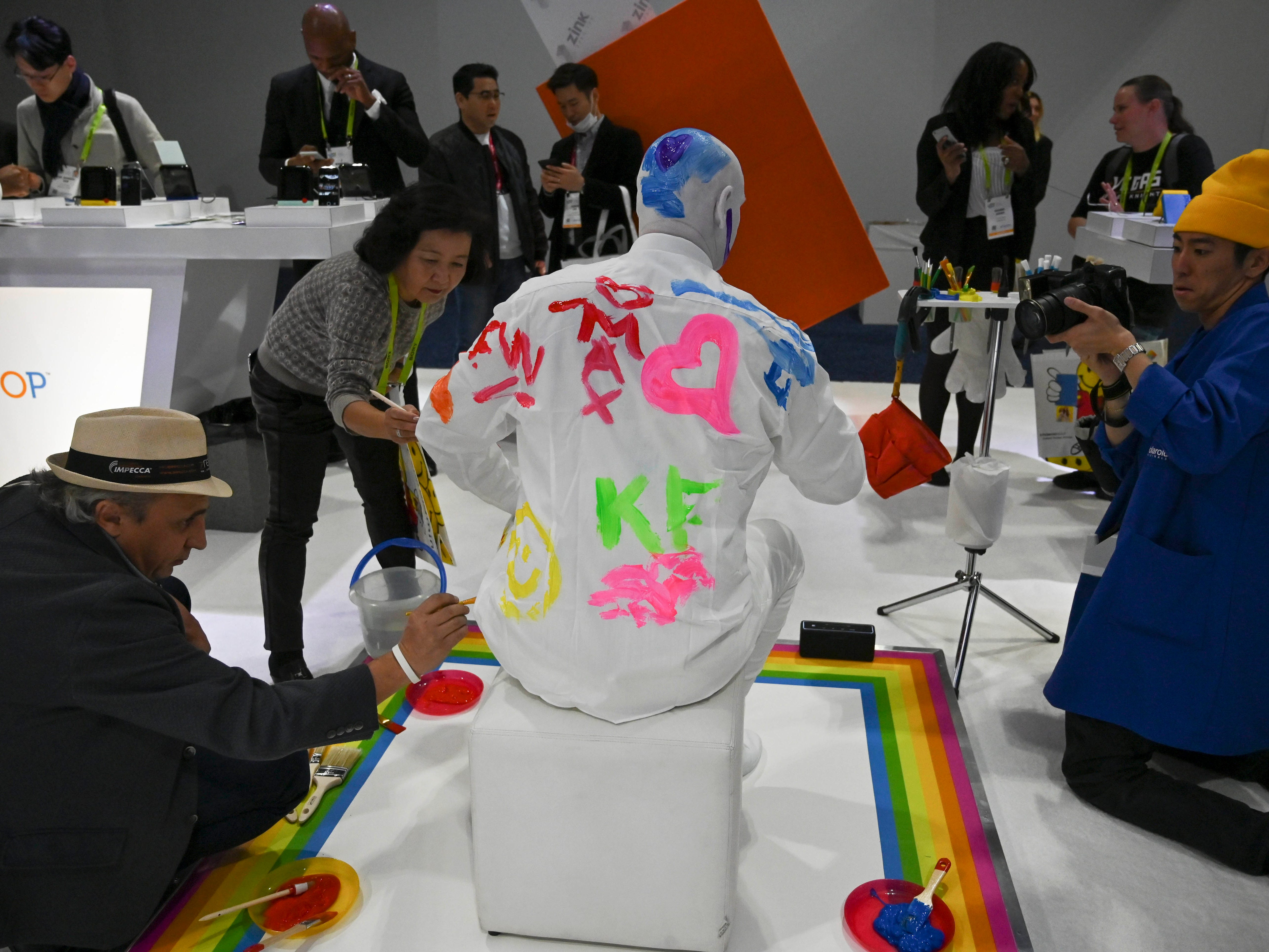 A model is painted at the Polaroid display.