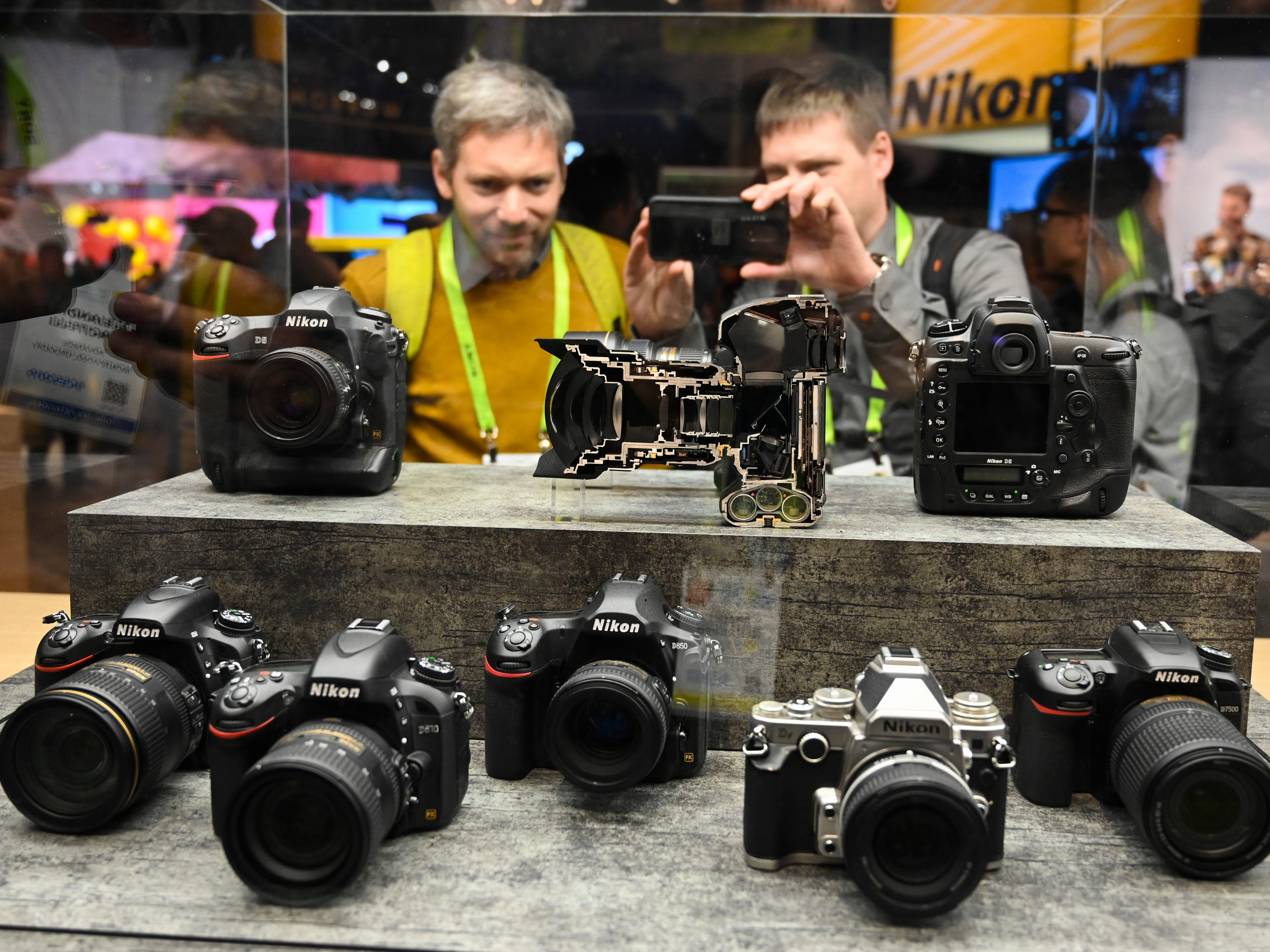 An attendee at CES 2019 takes a snapshot of digital cameras and lenses at the Nikon display.