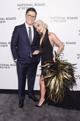 Presenter Stephen Colbert, left, and Lady Gaga embrace on the NBR red carpet.