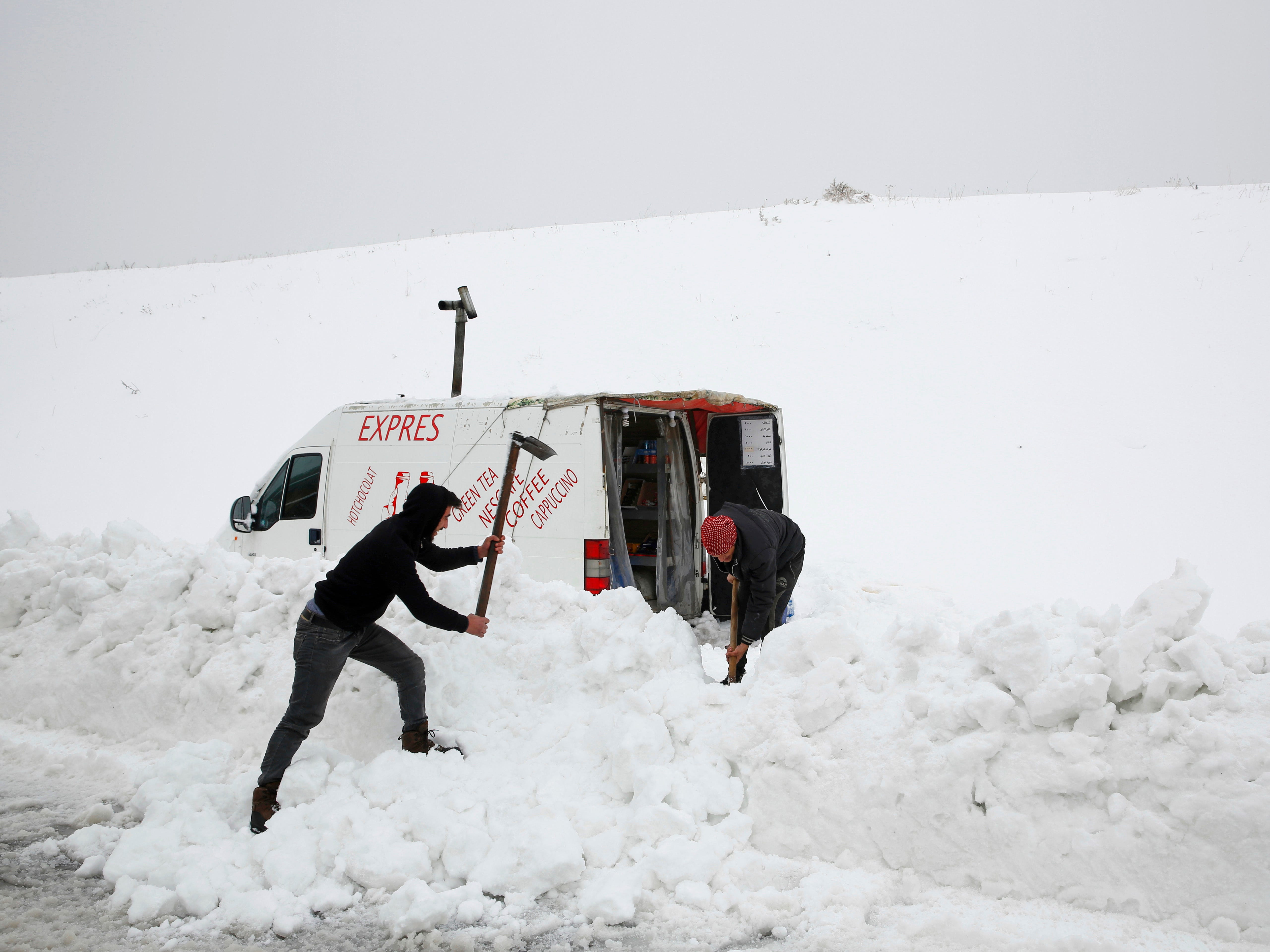 People remove snow to open a path to their van where they sell hot drinks, on the side of a highway in the village of Mdeirij, Mount Lebanon, Syria,  Jan 9. 2019.