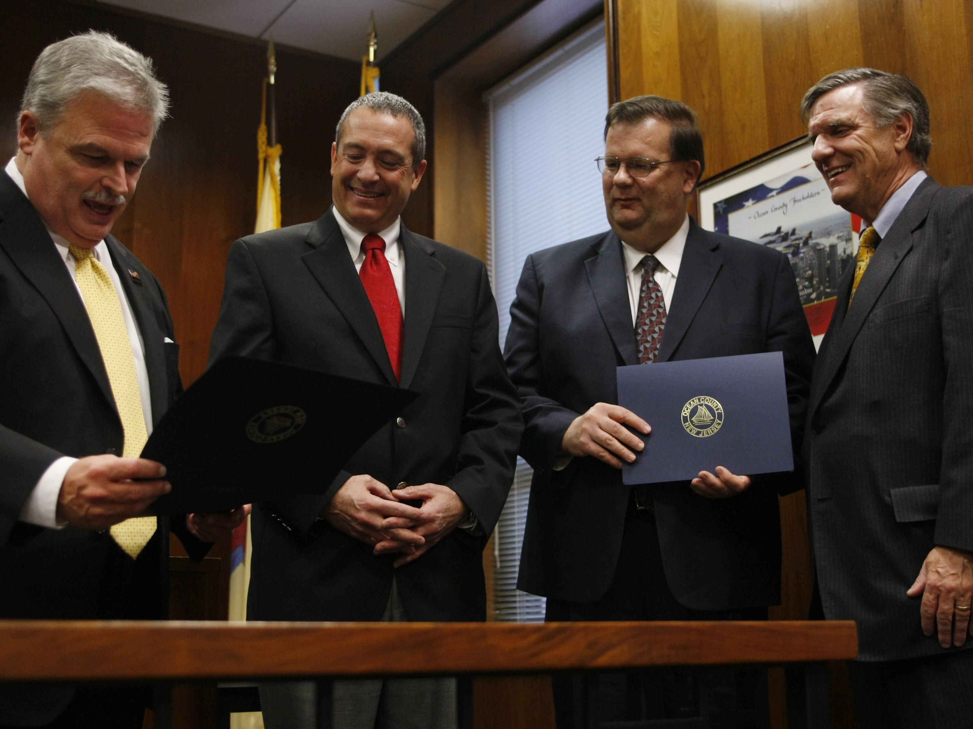Scott M. Colabella, Ocean County Clerk, left, reads the certificate of election presented to  Freeholders, James F. Lacey, second from left, and John P. Kelly, as George Gilmore, right, Ocean County Republican chairman and chairman of the Ocean County Board of Elections, looks on, during the Ocean County Board of Chosen Freeholders 2011 Organization Meeting, Wednesday, January 5, 2011. STAFF PHOTO/MARY FRANK - TOMS RIVER - #109381- NEWS/WEB - 01/05/11.
