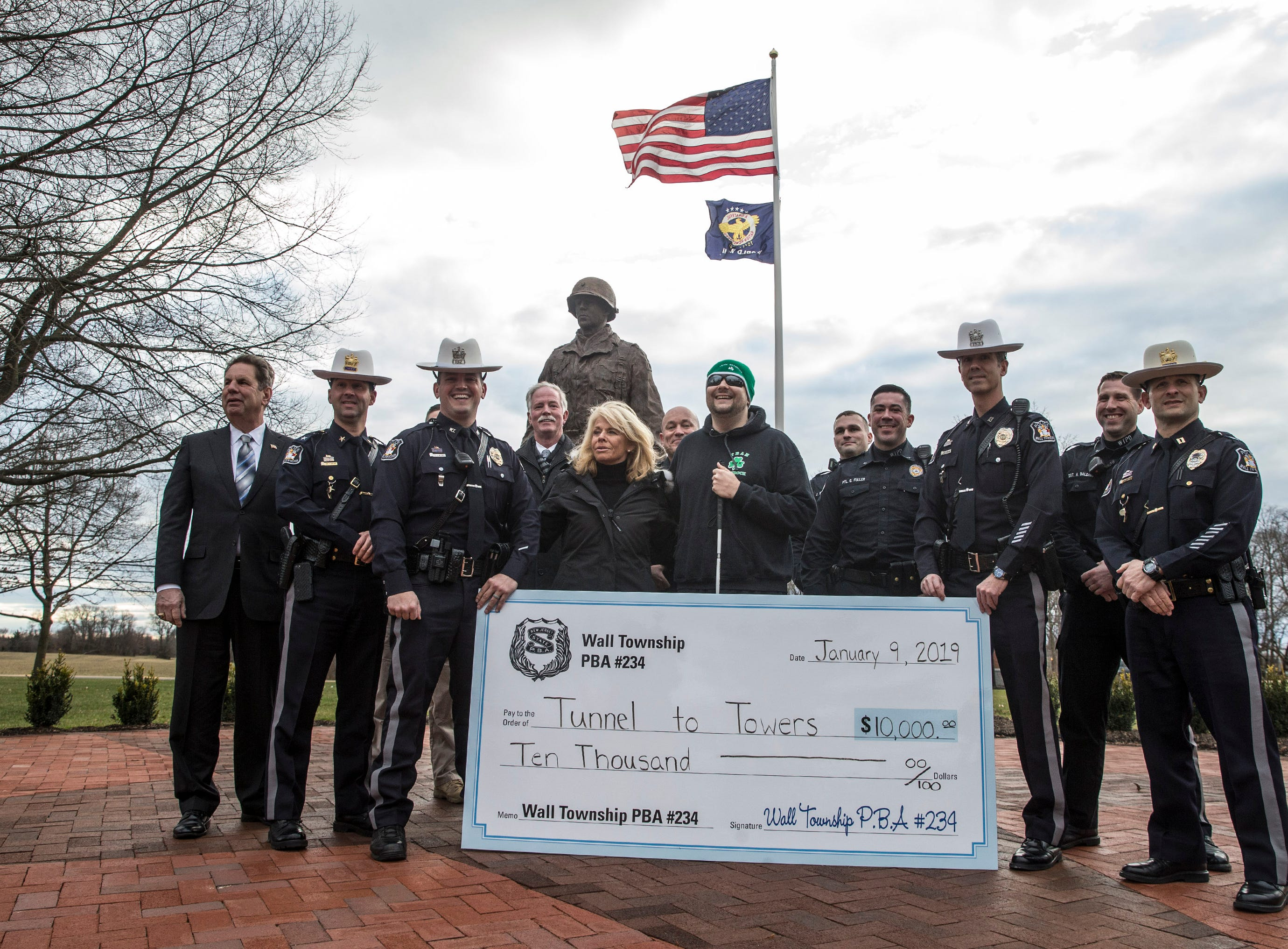 Wall Township police officer Mike Malone presents a $10,000 check to United States Marine Scott Nokes, a double-amputee, of Howell. The money is leftover from fundraising for the recently unveiled General Harry Rockafeller  statue in front of police headquarters. Also present is Kathy Cunningham of the Stephen Siller Tunnel to Towers Foundation which is building Nokes a smart home.  