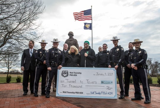 Wall Township police present a $10,000 check to former Marine Scott Nokes, a double-amputee, in front of the Gen. Harry Rockafeller statue at police headquarters. Also present is Kathy Cunningham of the Stephen Siller Tunnel to Towers Foundation.