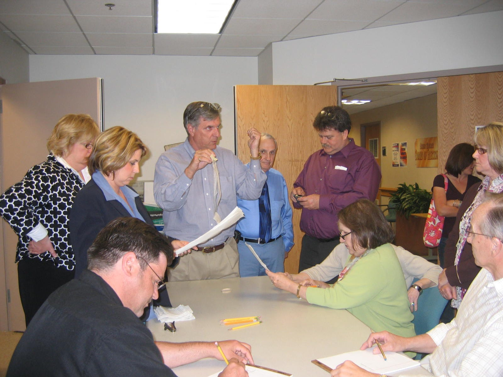 Times-Beacon photo by Paula Scully 5/12/09  George Gilmore, center, standing, and employees of the Ocean County Board of Elections, go over procedure for a vote recount May 12 in recount of write-in votes for the two top vote getters for a vacant three-year seat in the Little Egg Harbor School District elections April 21.