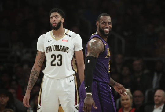 Los Angeles Lakers' LeBron James, right, smiles as he walks past New Orleans Pelicans' Anthony Davis during the first half of an NBA basketball game Dec. 21 in Los Angeles.