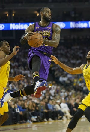 Los Angeles Lakers forward LeBron James (23) drives between Golden State Warriors' Kevon Looney (5) and Andre Iguodala during the first half of an NBA basketball game Dec. 25 in Oakland, Calif.