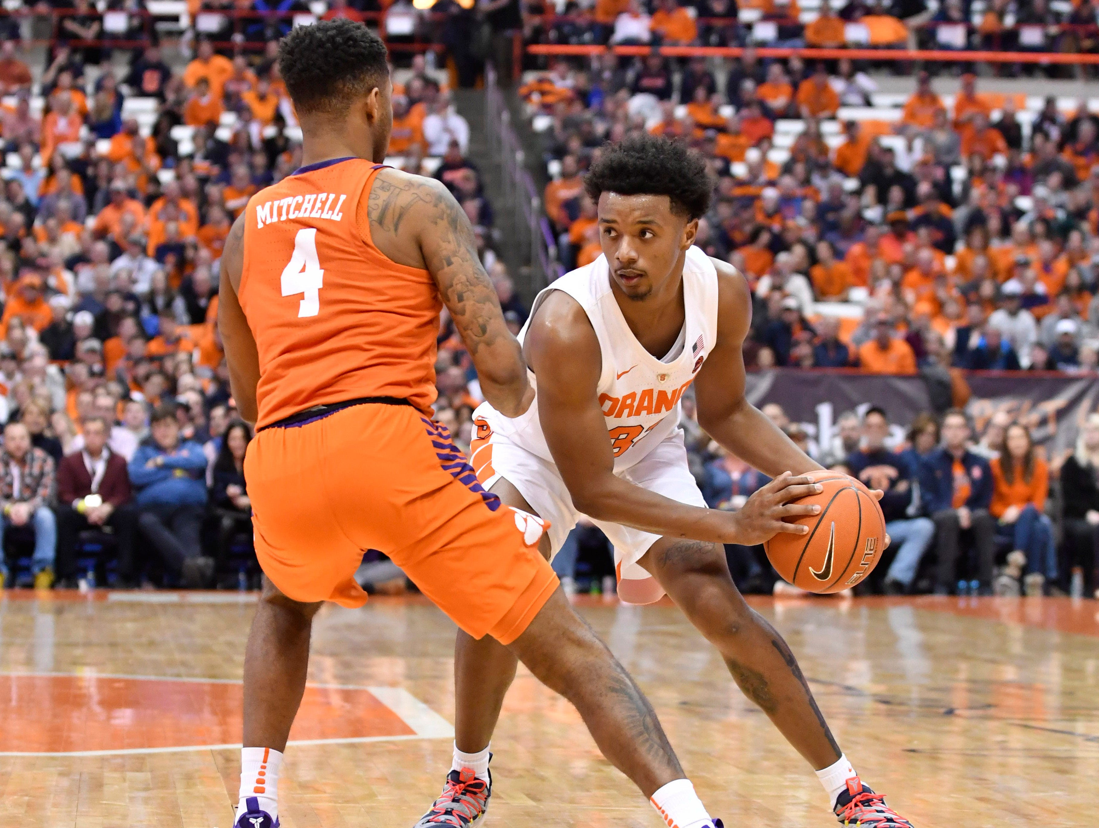 Jan 9, 2019; Syracuse, NY, USA; Syracuse Orange forward Elijah Hughes (33) sets up Clemson Tigers guard Shelton Mitchell (4) on the dribble during the second half at the Carrier Dome.