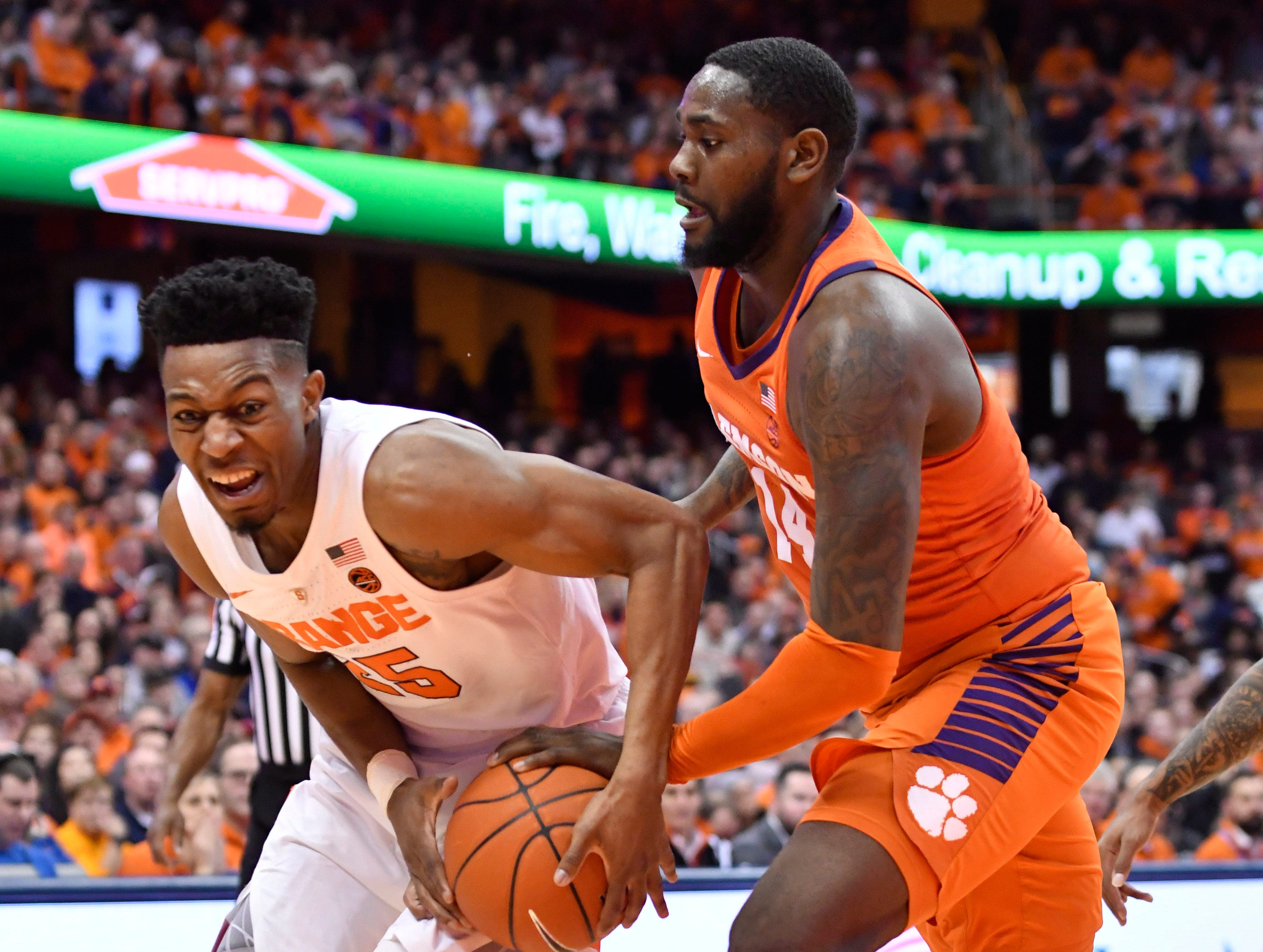 Jan 9, 2019; Syracuse, NY, USA; Syracuse Orange guard Tyus Battle (25) works to hold onto the ball against Clemson Tigers forward Elijah Thomas (14) during the second half at the Carrier Dome.