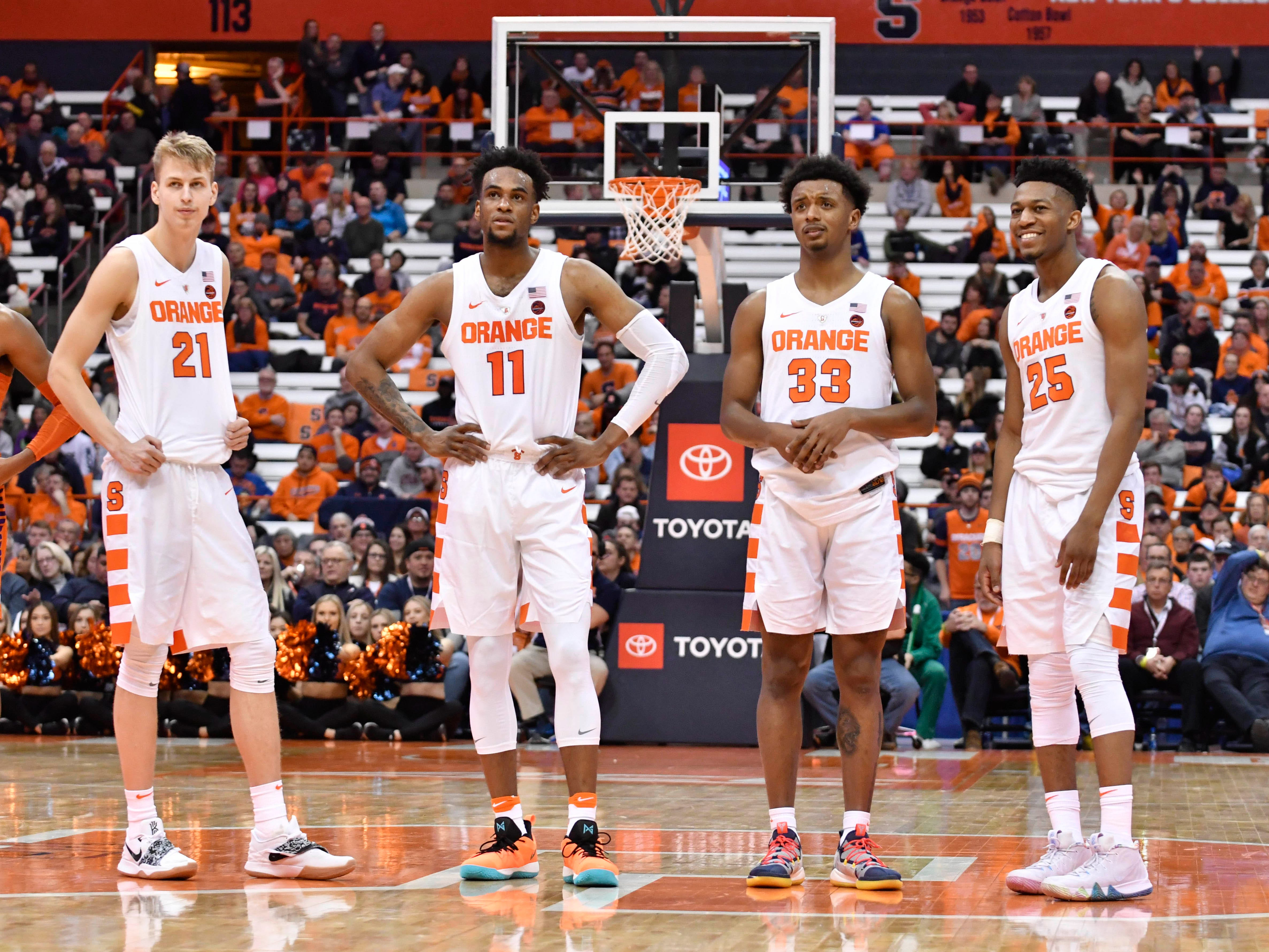 Jan 9, 2019; Syracuse, NY, USA; Four of Syracuse Orange starting team forward Marek Dolezaj (21) and forward Oshae Brissett (11) and forward Elijah Hughes (33) and guard Tyus Battle (25) watch a teammate take a free throw in the second half against the Clemson Tigers at the Carrier Dome.