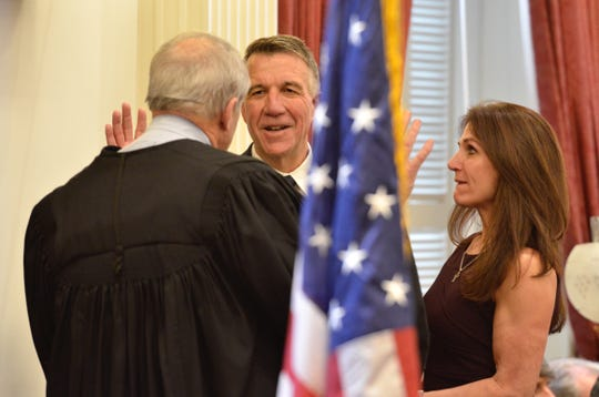 Gov. Phil Scott takes the oath of office alongside his wife, Diana McTeague Scott, on Jan. 10, 2019.