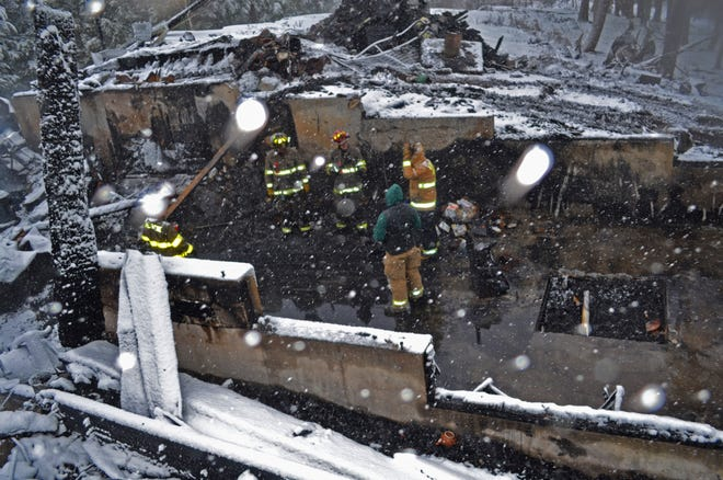 Fire investigators look through what's left of a barn at 2100 Harbor Road in Shelburne after a fire on Tuesday, Jan. 8, 2019, destroyed the structure. The Vermont State Police Department of Public Safety Fire & Explosion Investigation Unit is now considering the fire a possible act of arson.