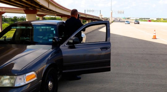 A Corpus Christi police officer uses a speed radar on a highway.
