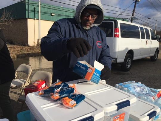 "John ""JB"" Brown prepares a harm reduction kit for a client at a needle exchange in Camden. Brown, a Newark native, lost two brothers to overdoses and two other brothers to AIDS related to their drug use."