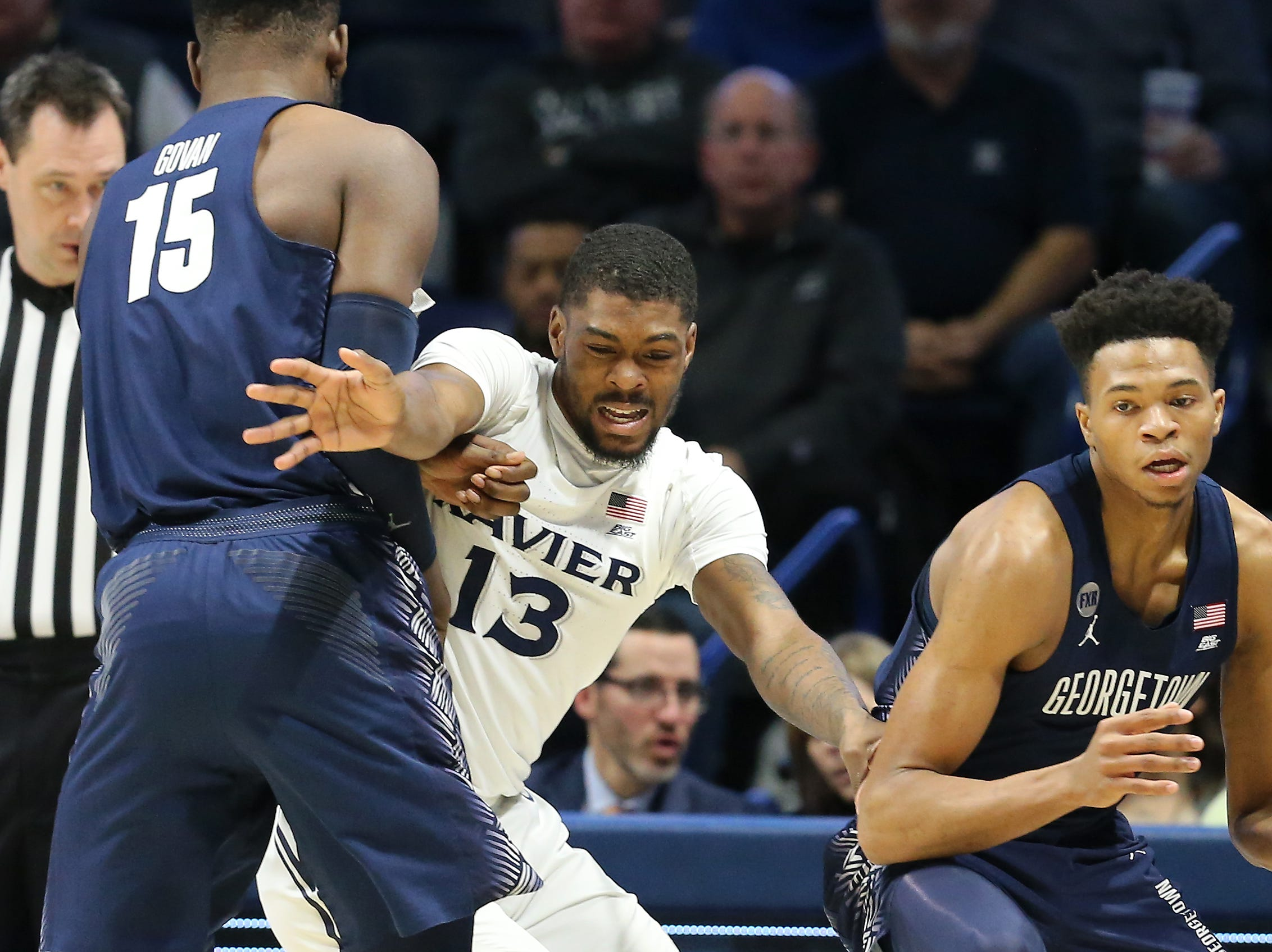 Xavier Musketeers forward Naji Marshall (13) fights through a screen by Georgetown Hoyas center Jessie Govan (15) in the first half of an NCAA basketball game, Wednesday, Jan. 9, 2019, at the Cintas Center in Cincinnati.