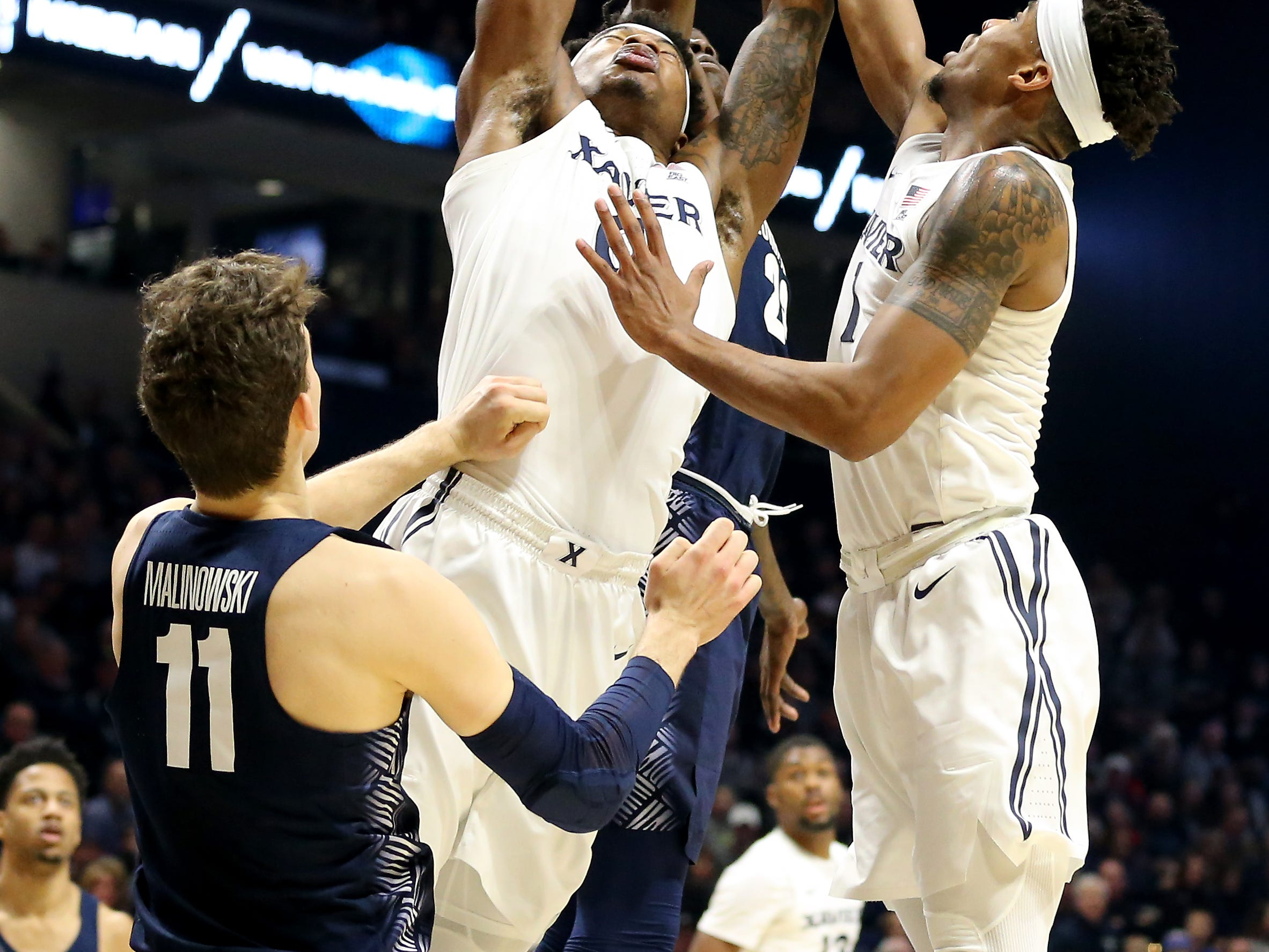 Xavier Musketeers forward Tyrique Jones (0) and Xavier Musketeers guard Paul Scruggs (1) go up for a rebound in the second half of an NCAA basketball game, Wednesday, Jan. 9, 2019, at the Cintas Center in Cincinnati. Xavier Musketeers won 81-75 against the Georgetown Hoyas.