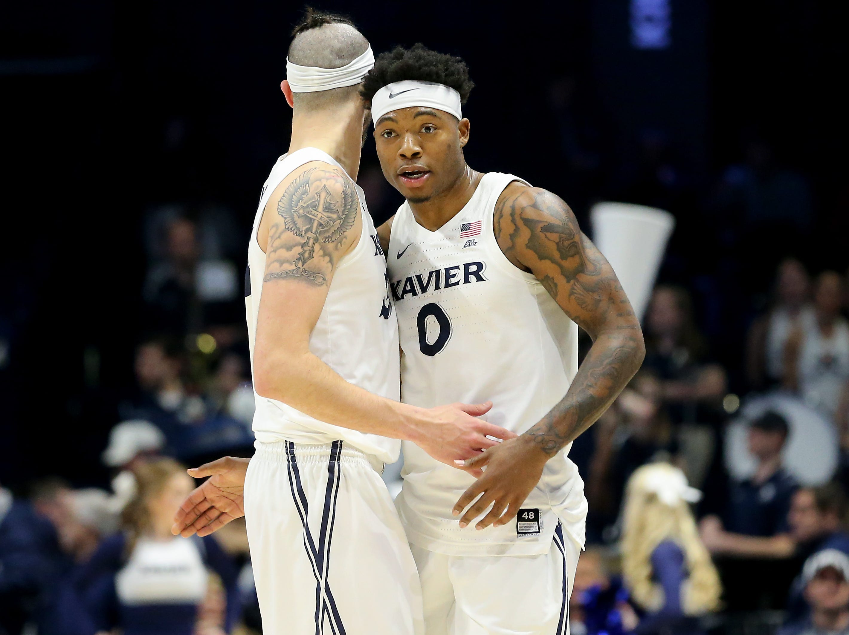 Xavier Musketeers forward Zach Hankins (35) and Xavier Musketeers forward Tyrique Jones (0) embrace in the second half of an NCAA basketball game, Wednesday, Jan. 9, 2019, at the Cintas Center in Cincinnati. Xavier Musketeers won 81-75 against the Georgetown Hoyas.