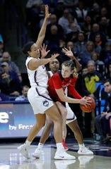 Cincinnati Bearcats guard Sam Rodgers (11) looks for an opening against Connecticut Huskies forward Napheesa Collier (24) and guard Christyn Williams (13) in the first quarter at Gampel Pavilion.
