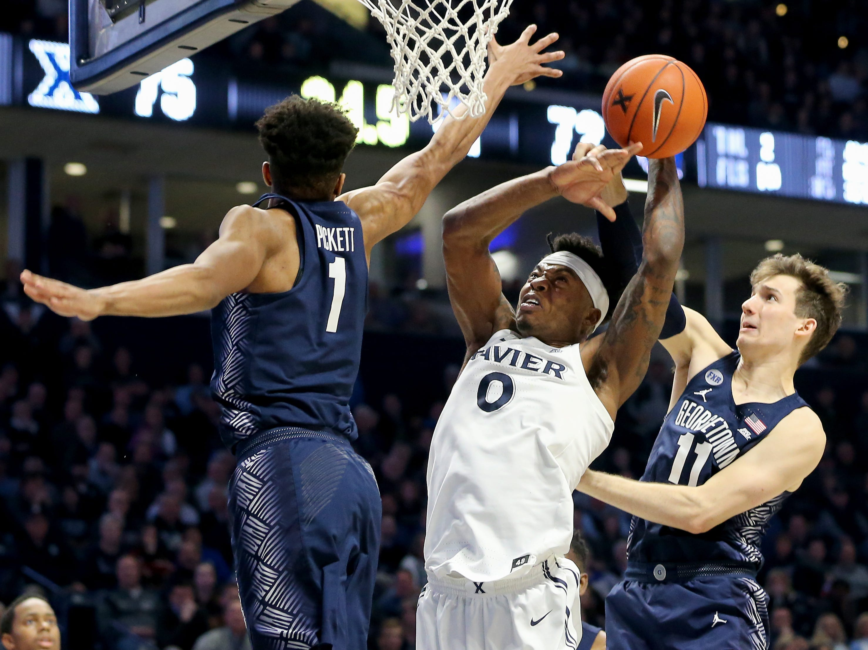 Xavier Musketeers forward Tyrique Jones (0) rises to the basket as Georgetown Hoyas guard Jamorko Pickett (1) and Georgetown Hoyas guard Greg Malinowski (11) defends in the second half of an NCAA basketball game, Wednesday, Jan. 9, 2019, at the Cintas Center in Cincinnati. Xavier Musketeers won 81-75 against the Georgetown Hoyas.