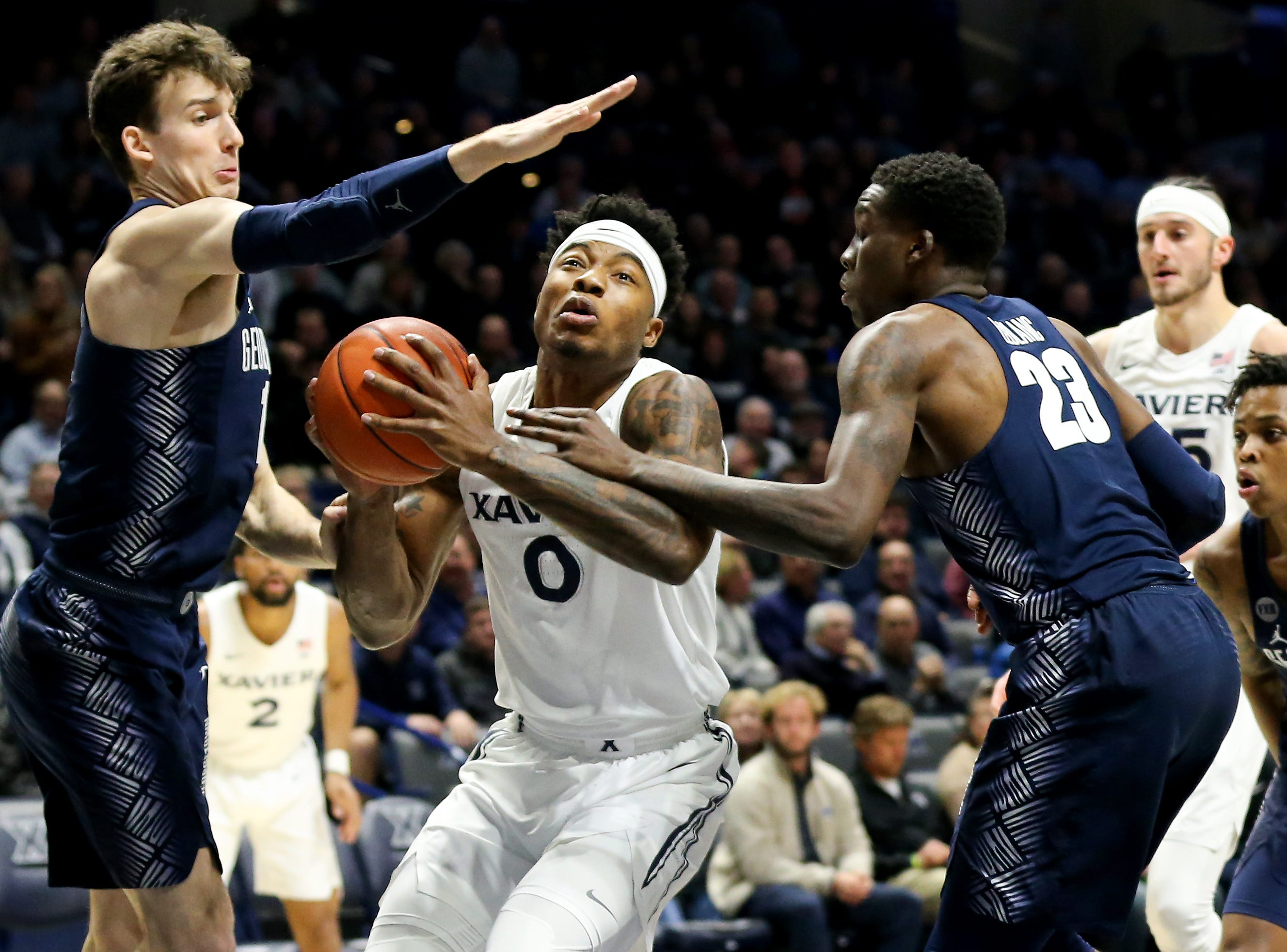 Xavier Musketeers forward Tyrique Jones (0) splits two defenders in the first half of an NCAA basketball game against the Georgetown Hoyas, Wednesday, Jan. 9, 2019, at the Cintas Center in Cincinnati.