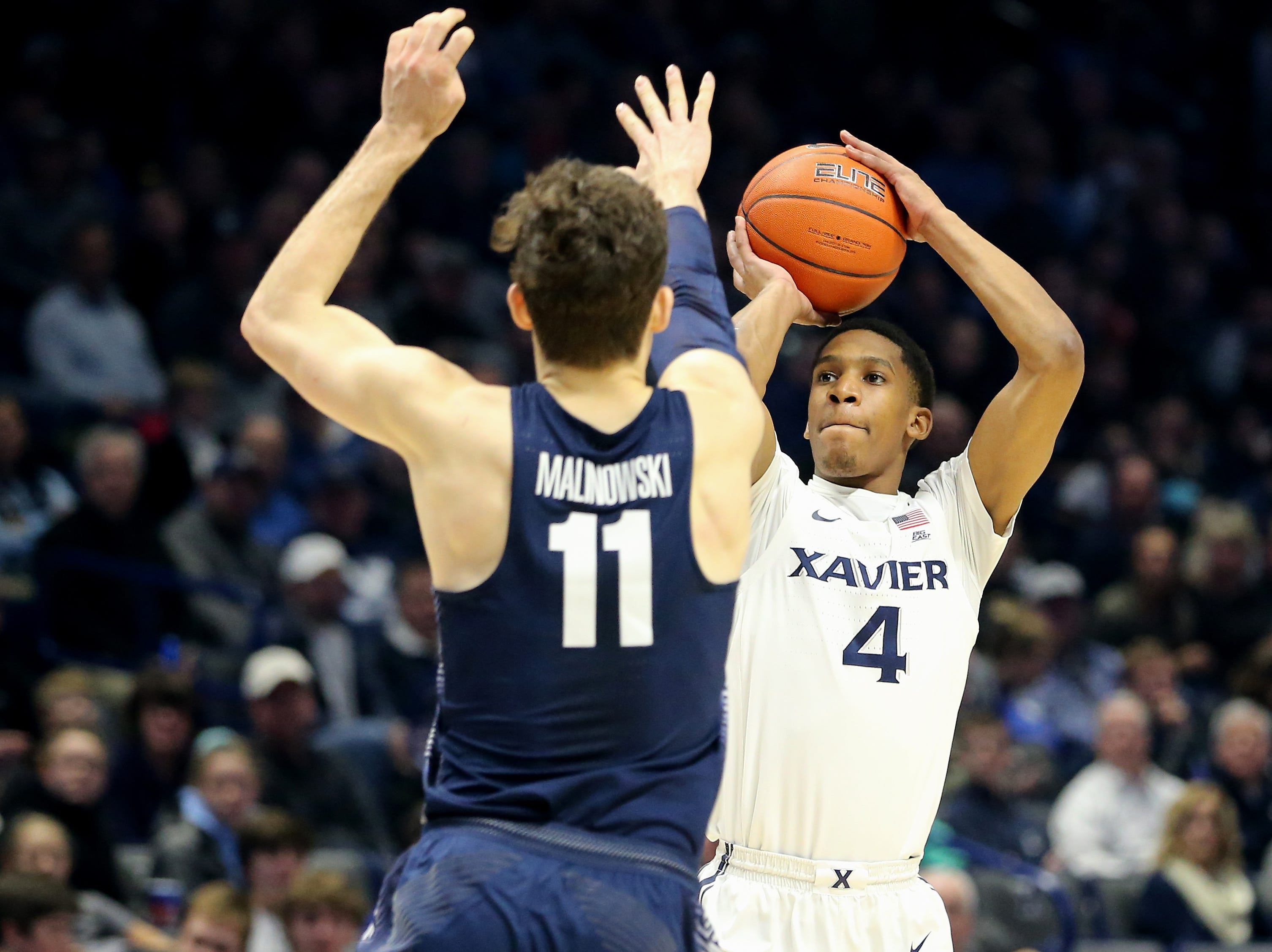 Xavier Musketeers guard Elias Harden (4) rises for a 3-point shot over Georgetown Hoyas guard Greg Malinowski (11) in the second half of an NCAA basketball game, Wednesday, Jan. 9, 2019, at the Cintas Center in Cincinnati. Xavier Musketeers won 81-75 against the Georgetown Hoyas.