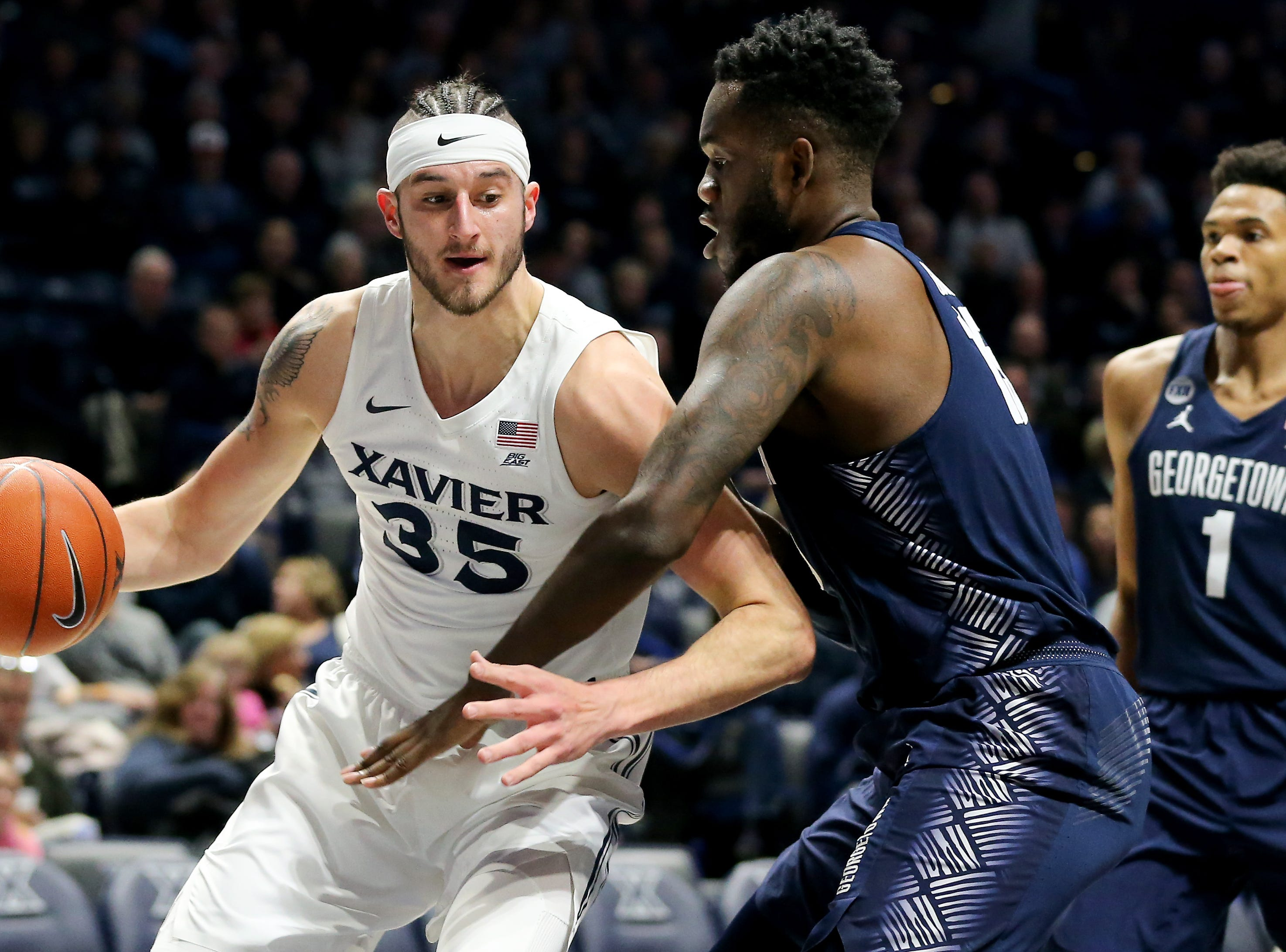 Xavier Musketeers forward Zach Hankins (35) spins toward the basket as Georgetown Hoyas center Jessie Govan (15) defends in the first half of an NCAA basketball game, Wednesday, Jan. 9, 2019, at the Cintas Center in Cincinnati.