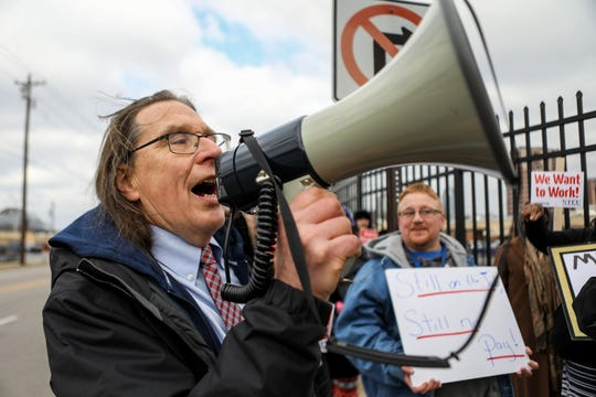 Mike McAuley shouts through a megaphone with protestors of the government shutdown. Government employees, National Treasury  Employee Unions members and citizens gather in Covington, KY outside of the IRS building to protest the government shutdown on Thursday Jan, 10, 2019.